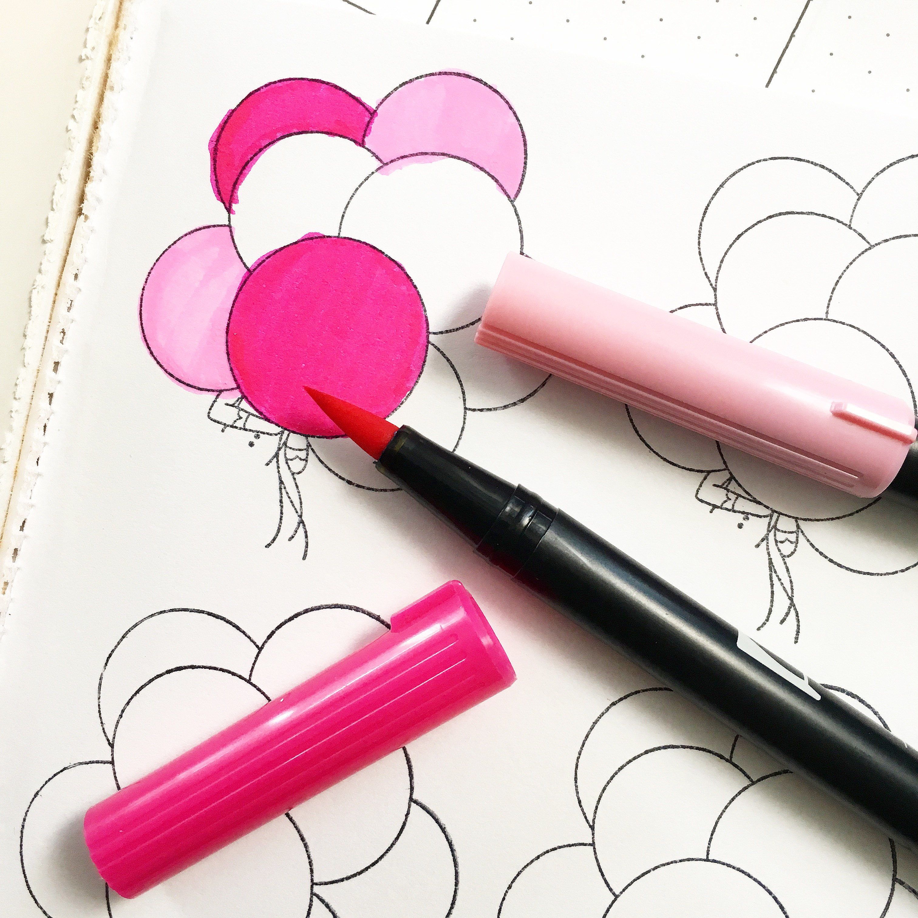 colouring stamped balloons in dark and light pink using brush markers