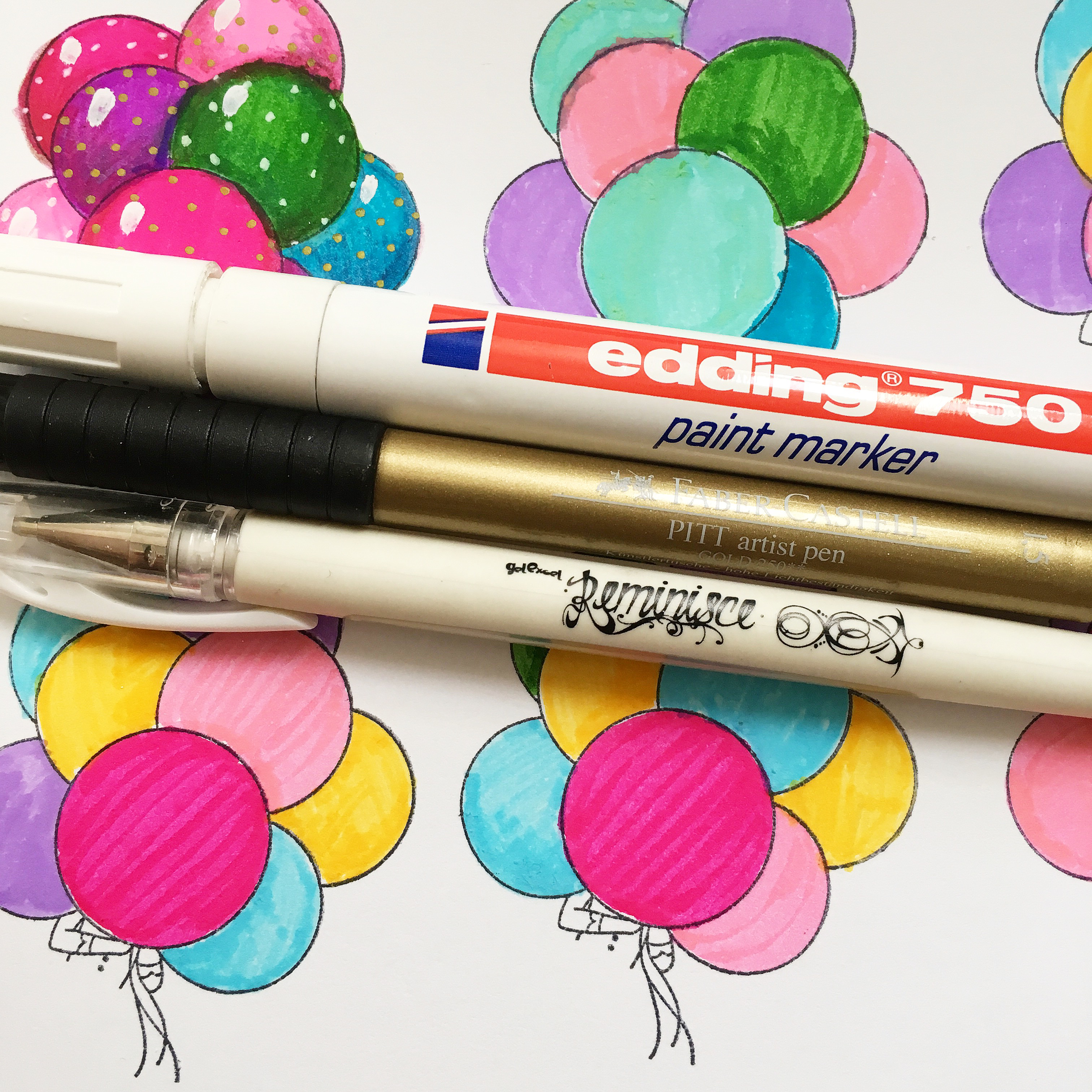 White paint marker, golden ink marker, white pen. In the background - coloured balloons in green, pink, blue, yellow and purple.