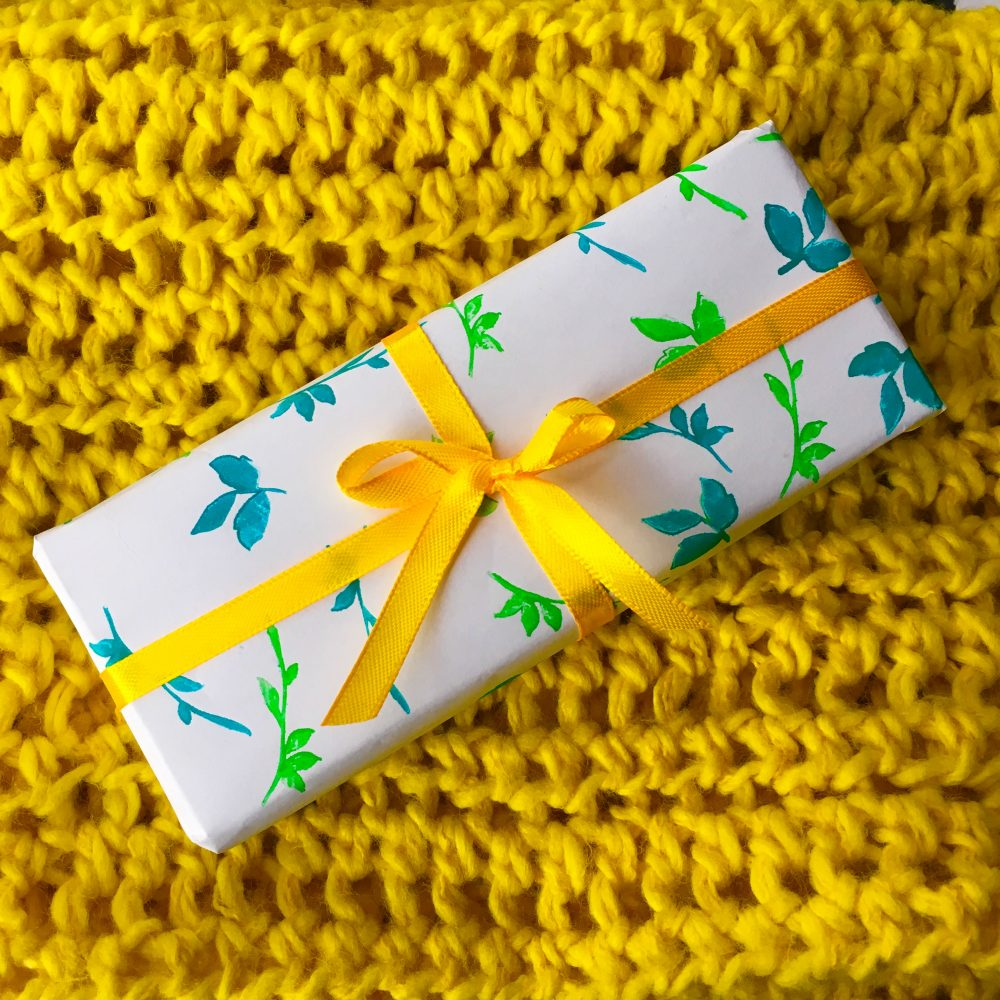 bright yellow crocheted scarf and gift wrapped in white-green-blue paper and yellow ribbon