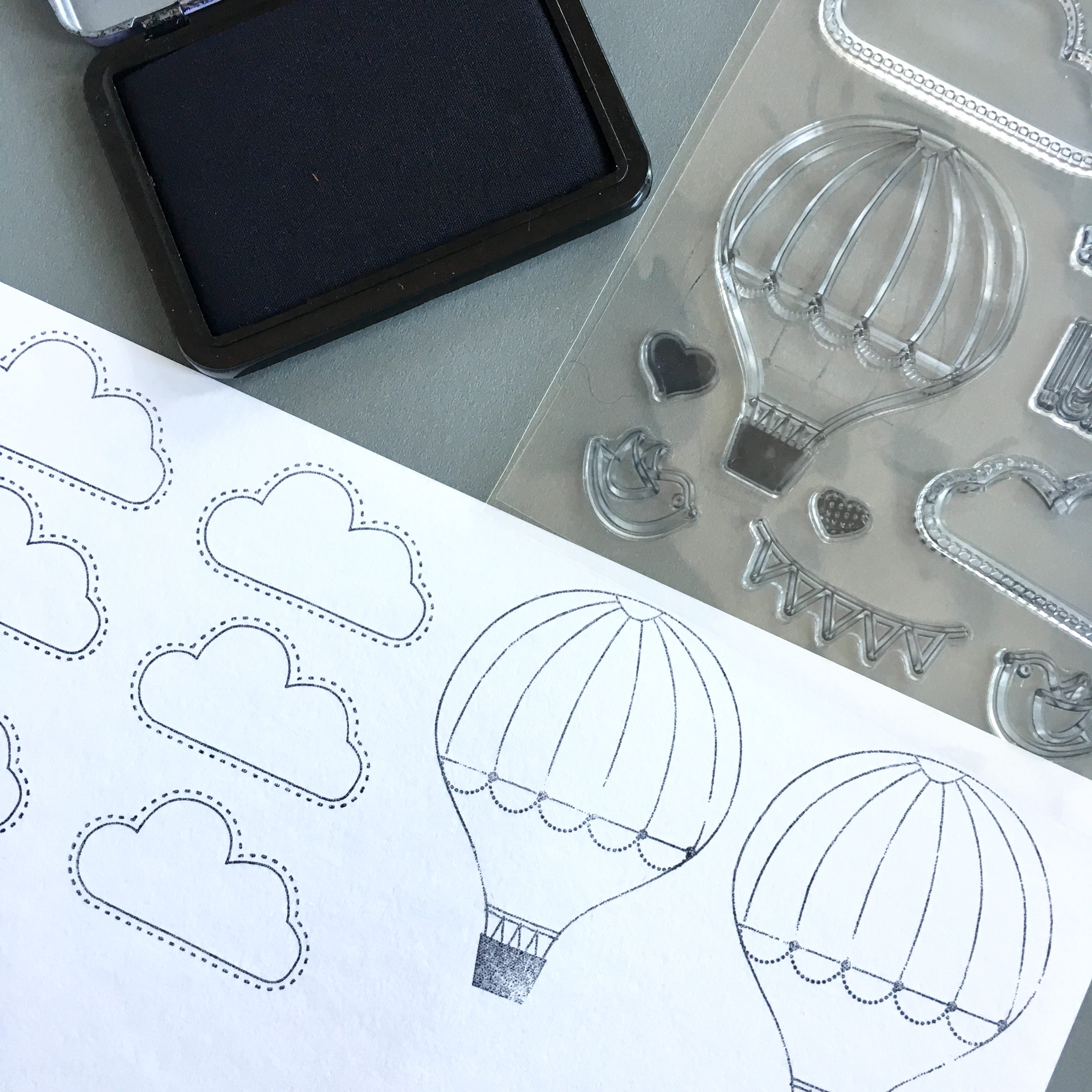 black and white picture of white paper, black ink pad and stamps with hot air balloons and clouds in black