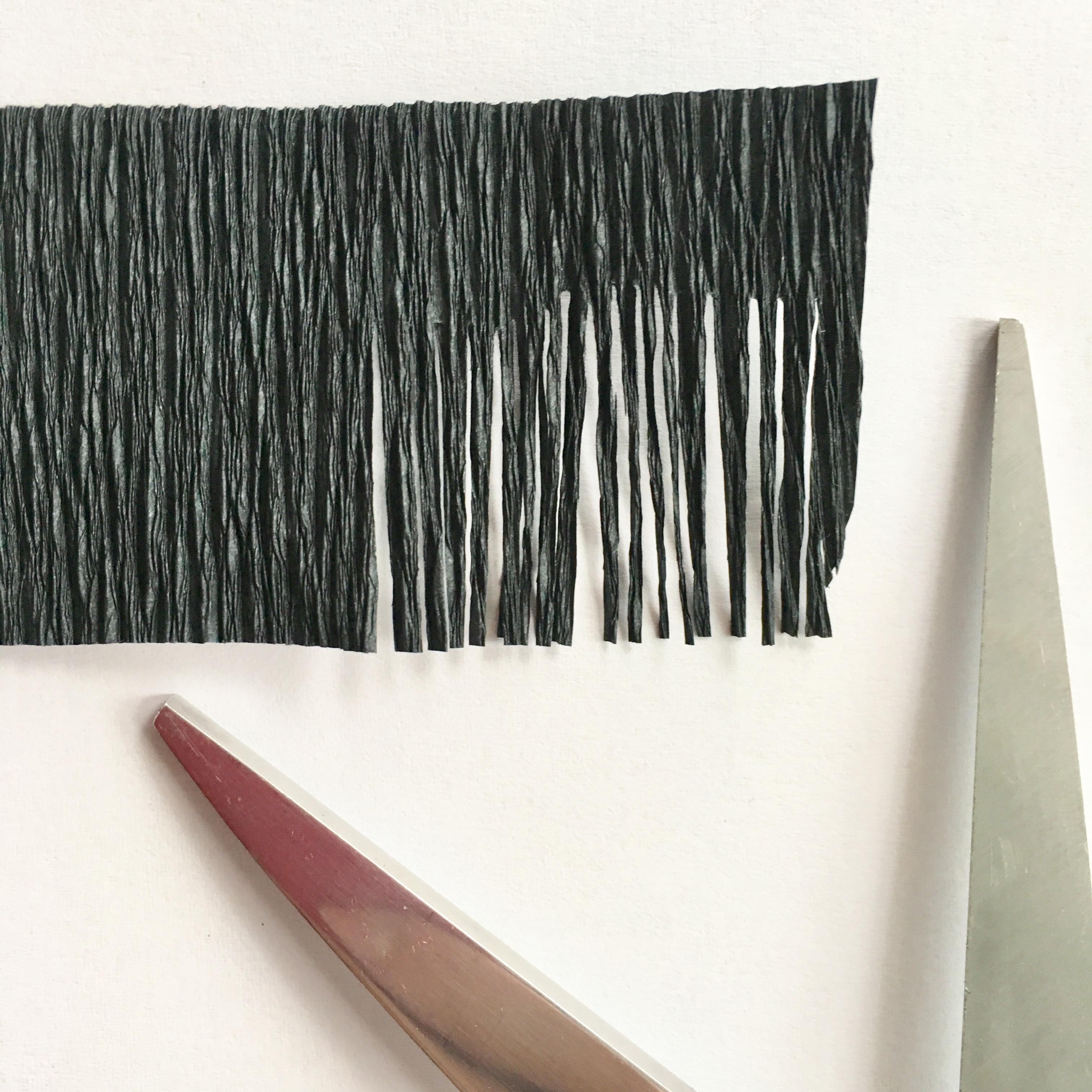 cut fringes on black crepe paper piece