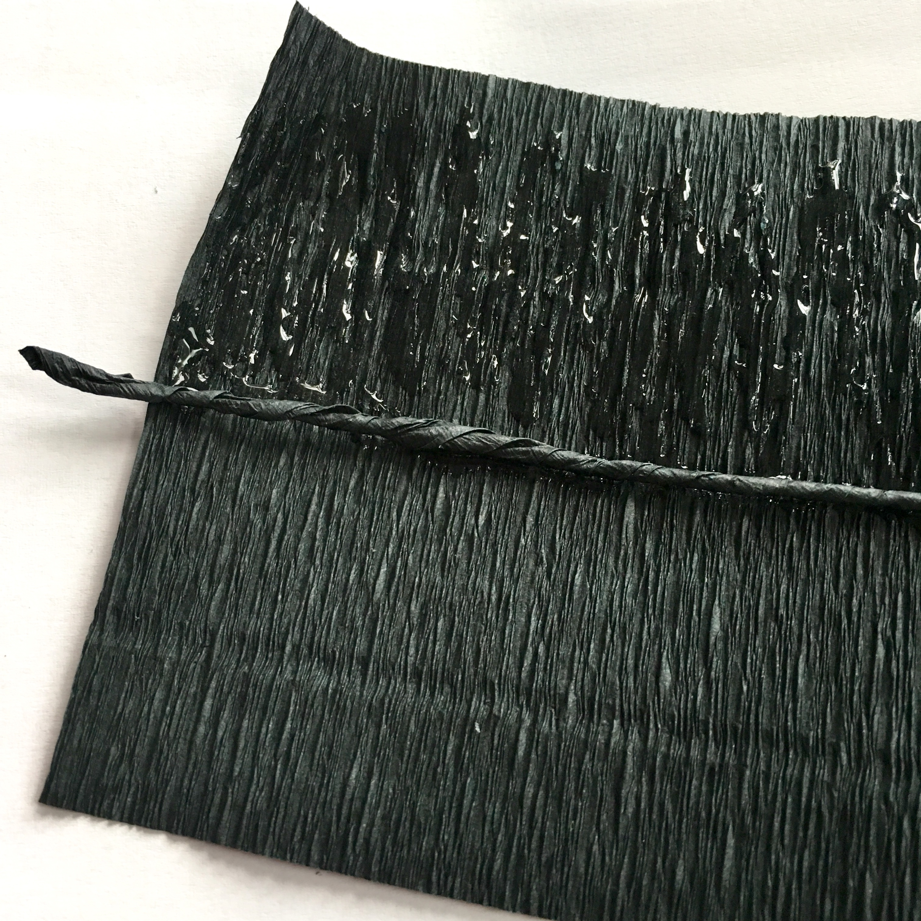 gluing string of twisted crepe paper in the middle of black crepe paper - making more stamens