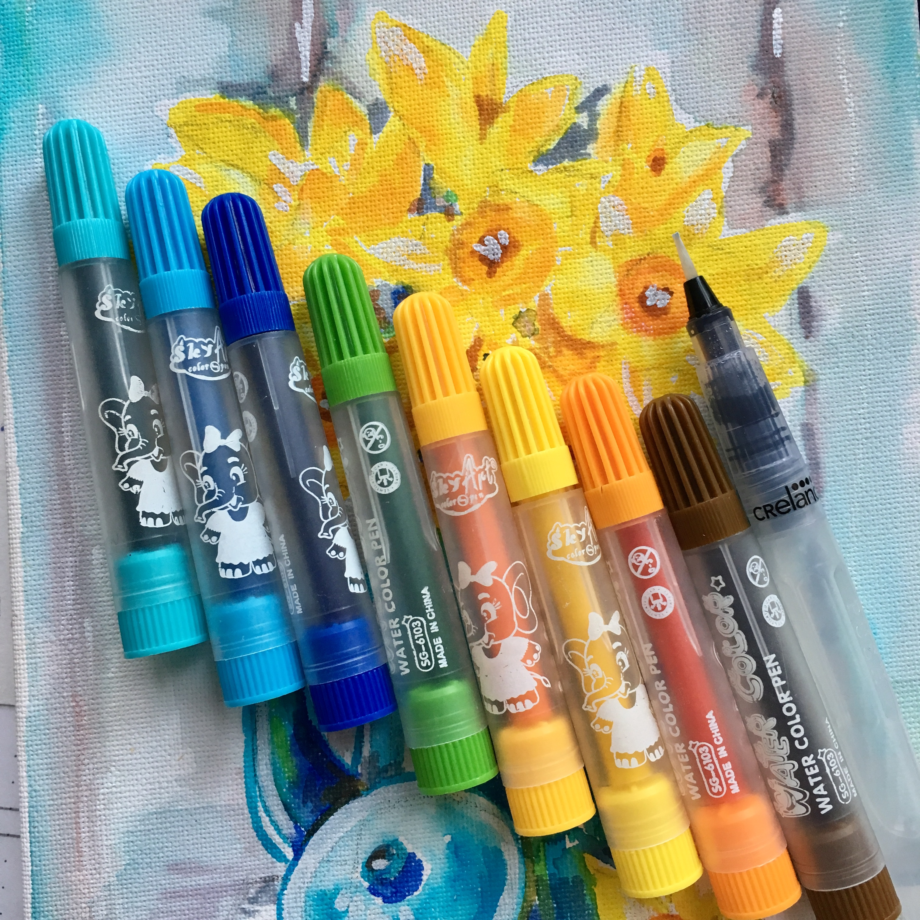 yellow daffodils with watercolour markers in blue, green and orange