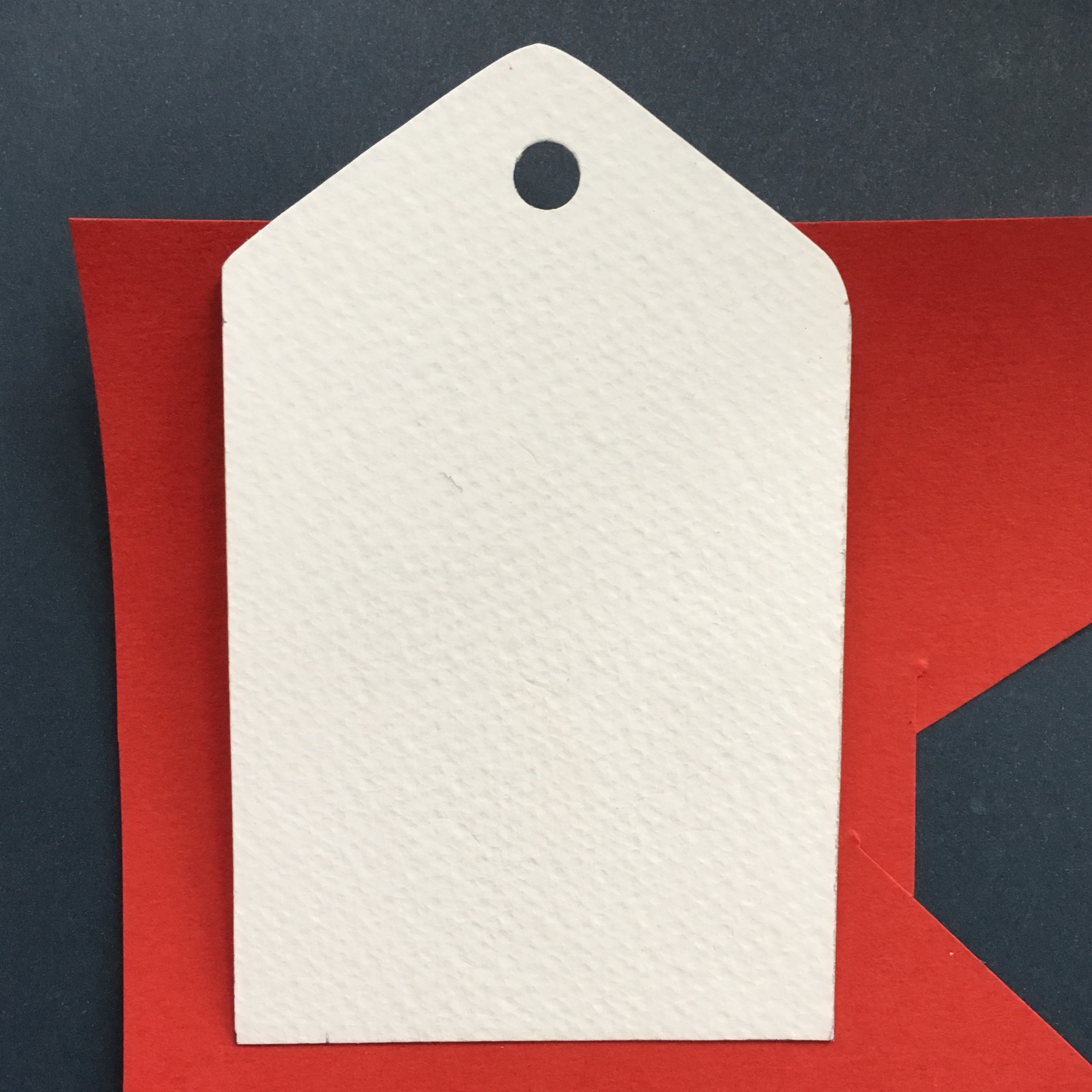 white paper gift tag on red background