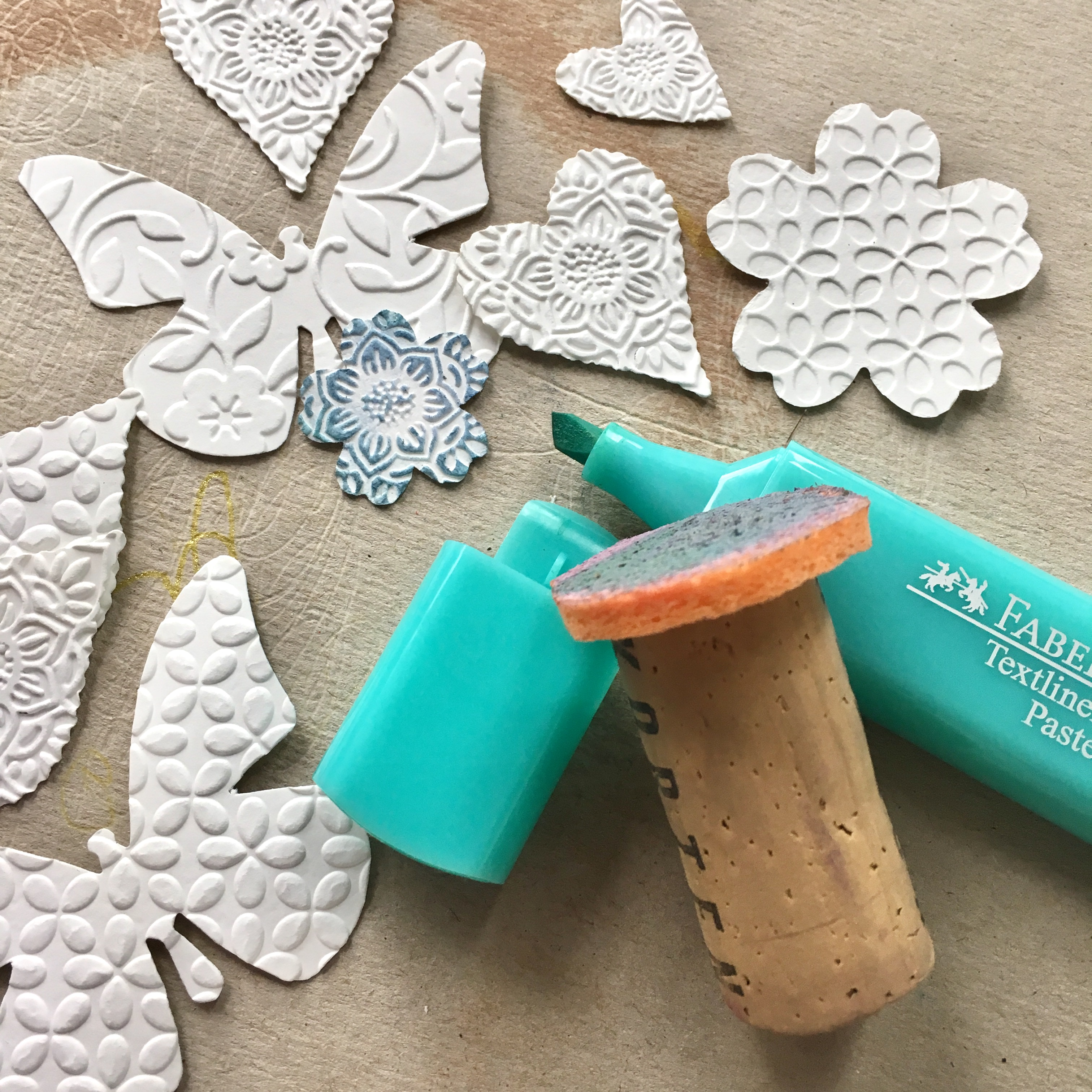 embossed paper butterflies, flowers and hearts, turquoise textliner and blending tool from cork and sponge