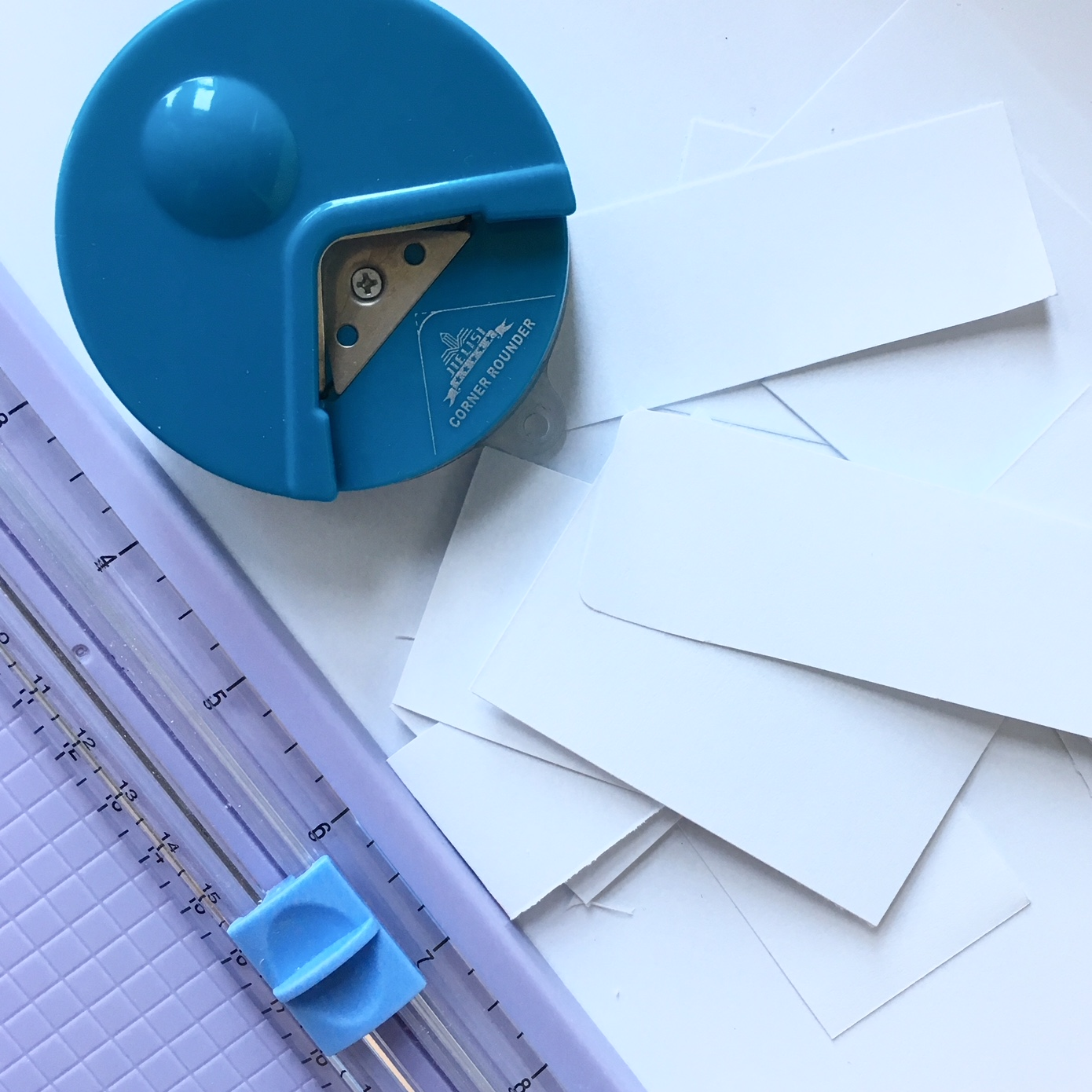 white paper rectangles, blue round edge cutter and a paper guillotine