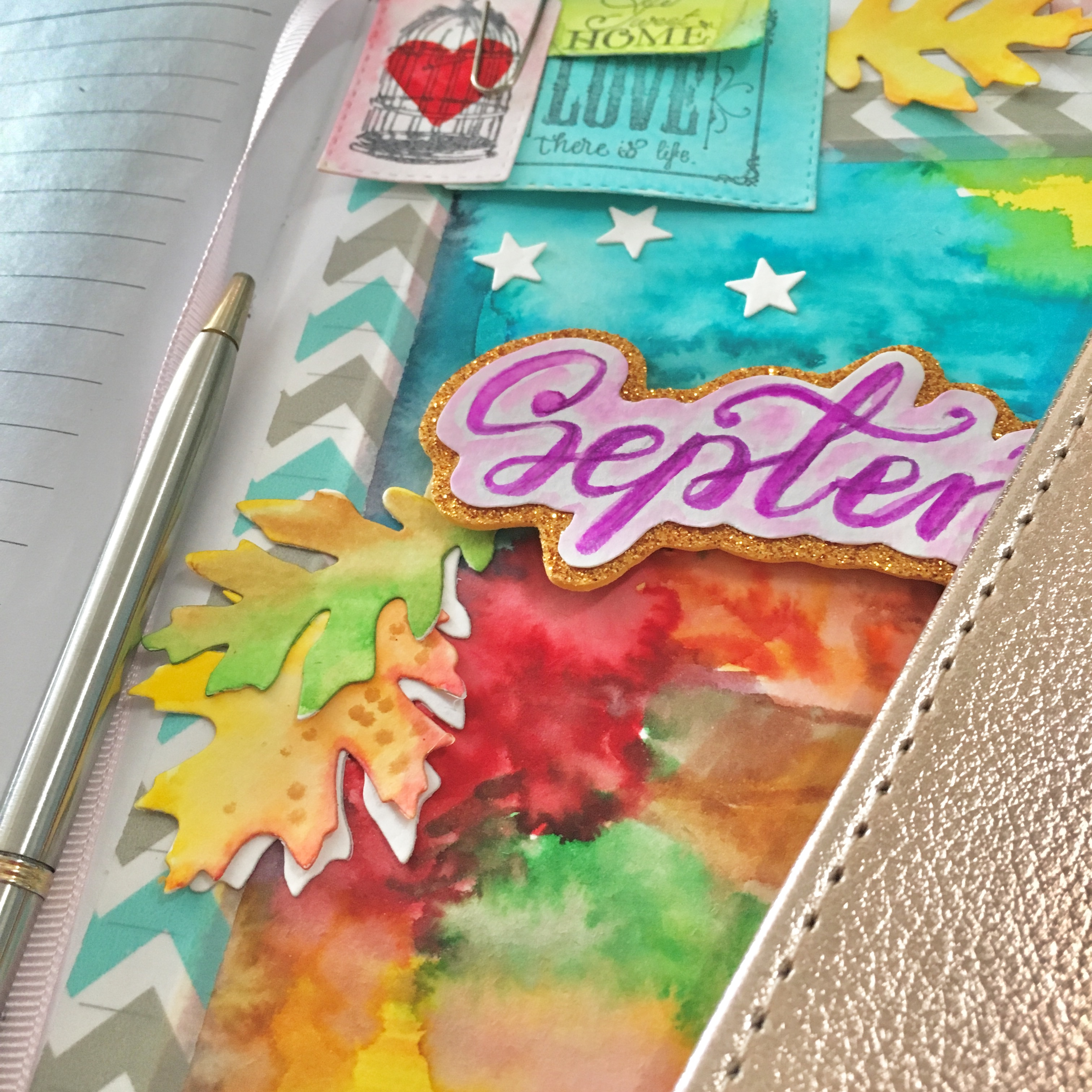 colourful (blue, orange, yellow, red, pink, purple) title page of bullet journal. The sign is September - in purple. There are some glued elements like white stars and yellow and green leaves