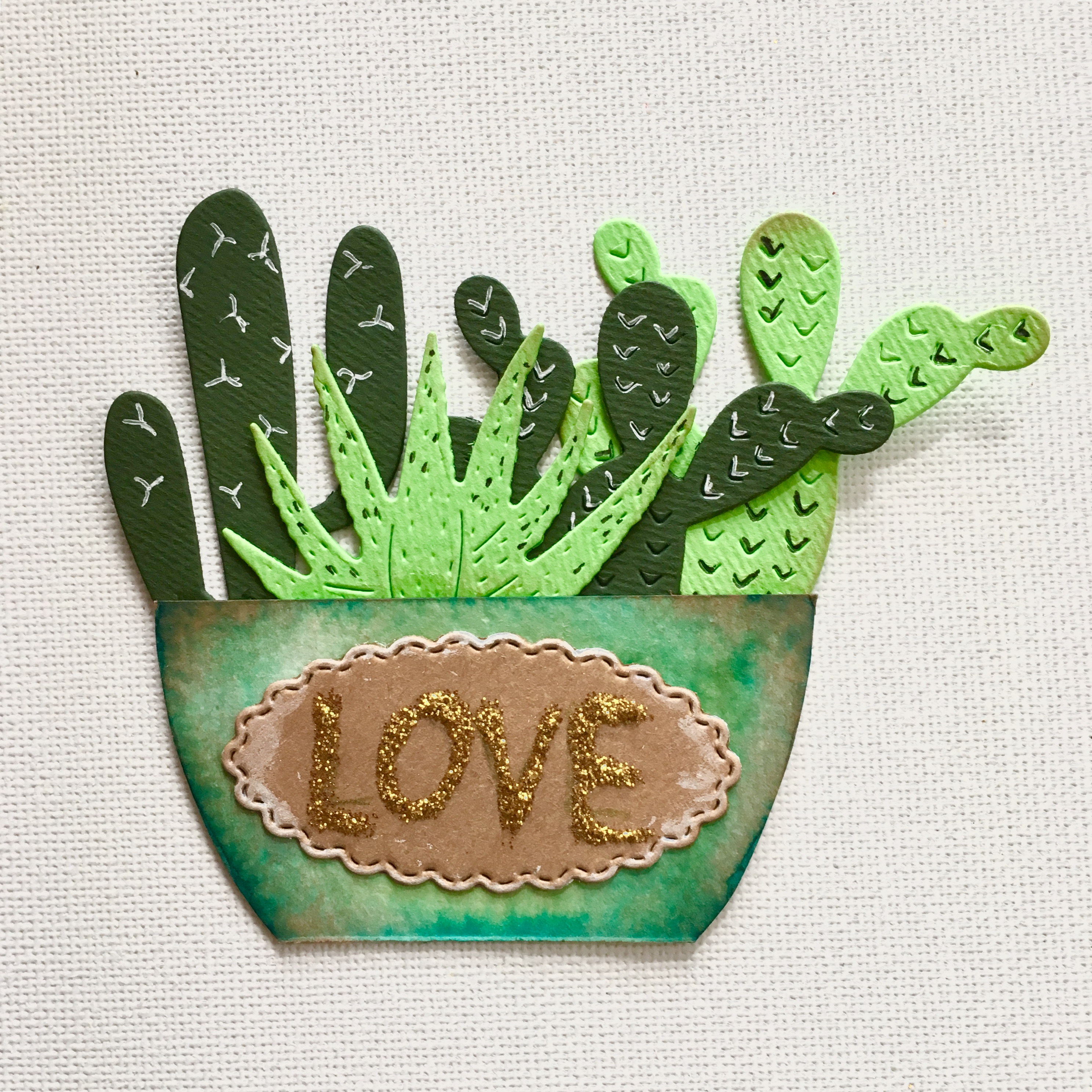one finished cactus embellishment - turquoise brown pot and green cactuses with label LOVE