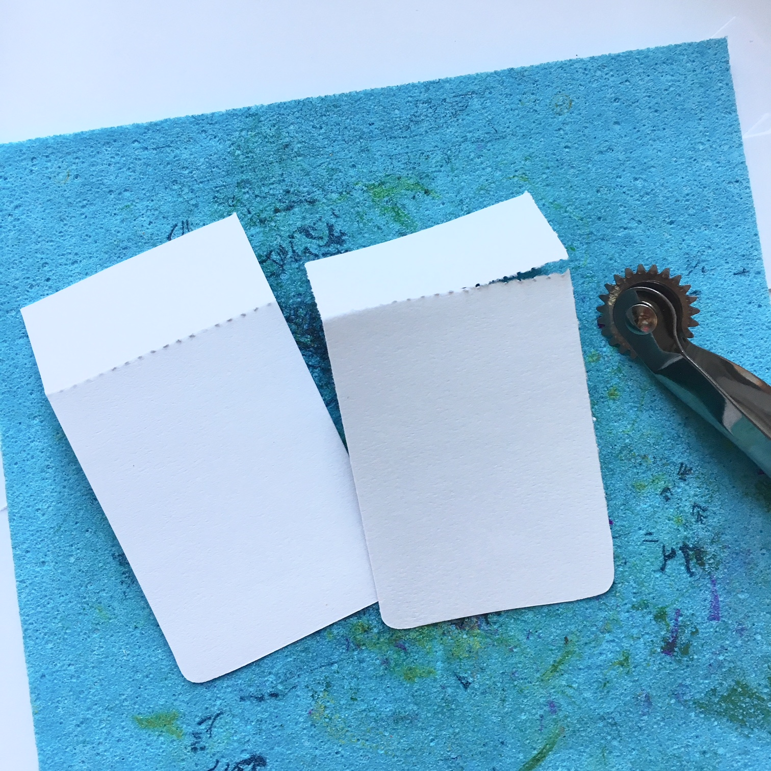 two rectangles from white paper with round edges and a little knife for paper perforation