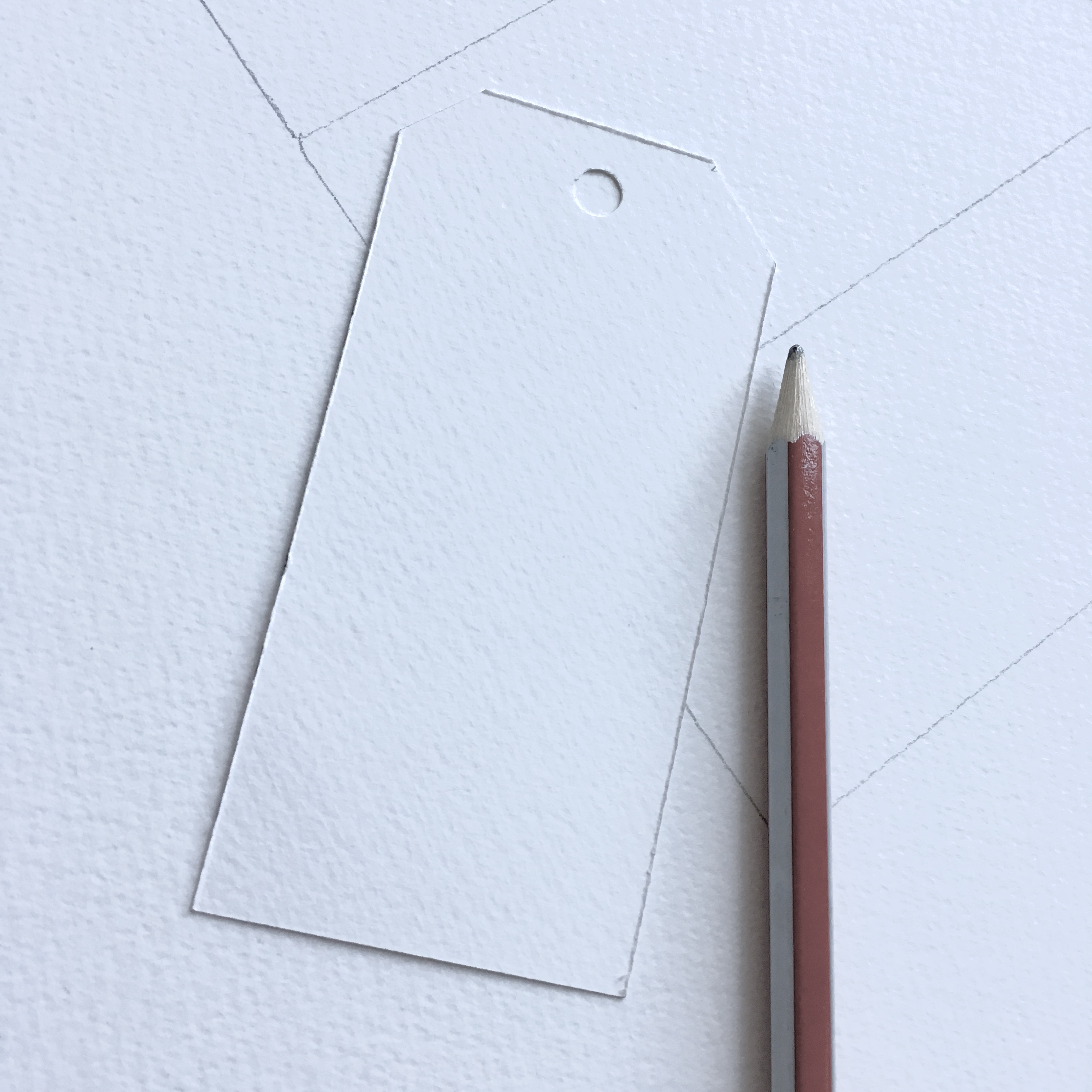 white watercolour paper with shapes of gift tags drawn and a single gift tag already cut