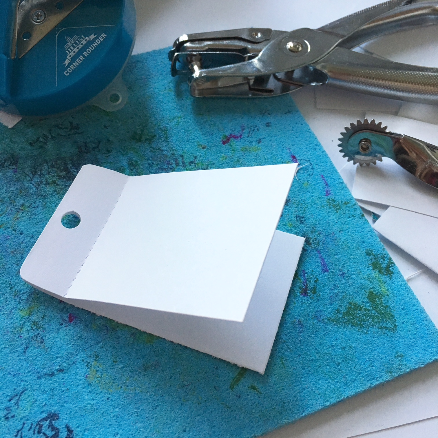 folded rectangular piece of paper whith a punch hole, punch hole maker, perforation knife and edge punch