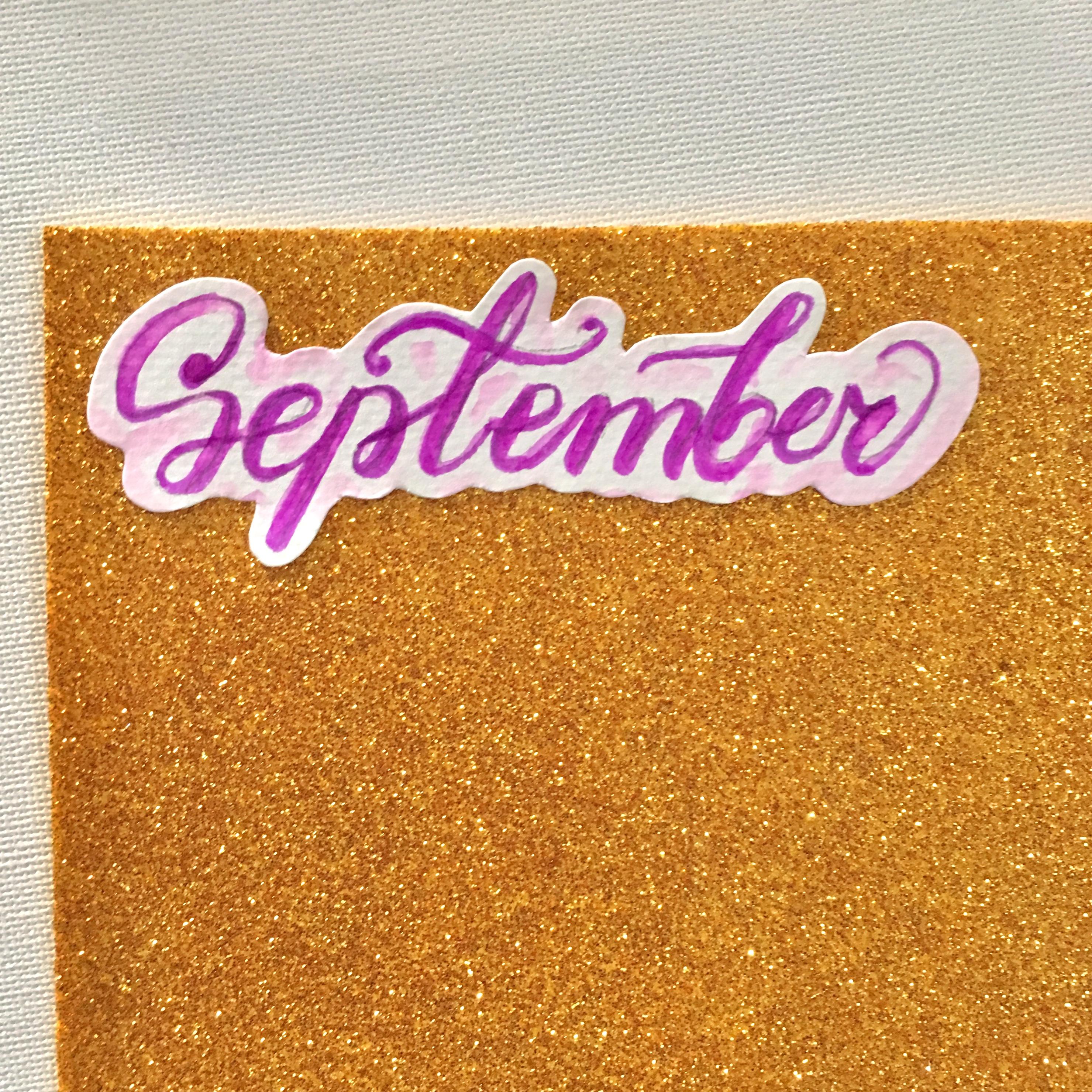 the purple handwritten sign September, glued on a glitter foam