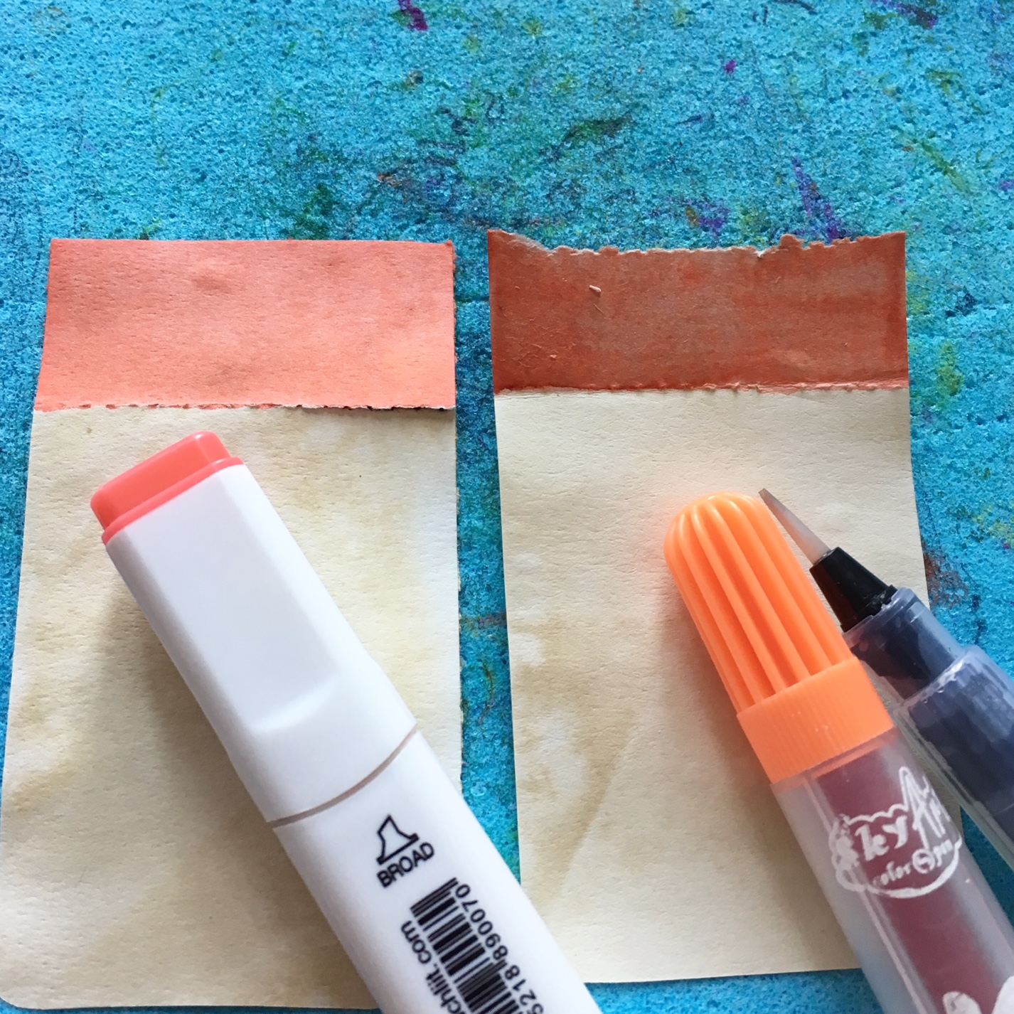 colouring part of the paper rectangles with orange alcoholic marker and water markers and water container brush