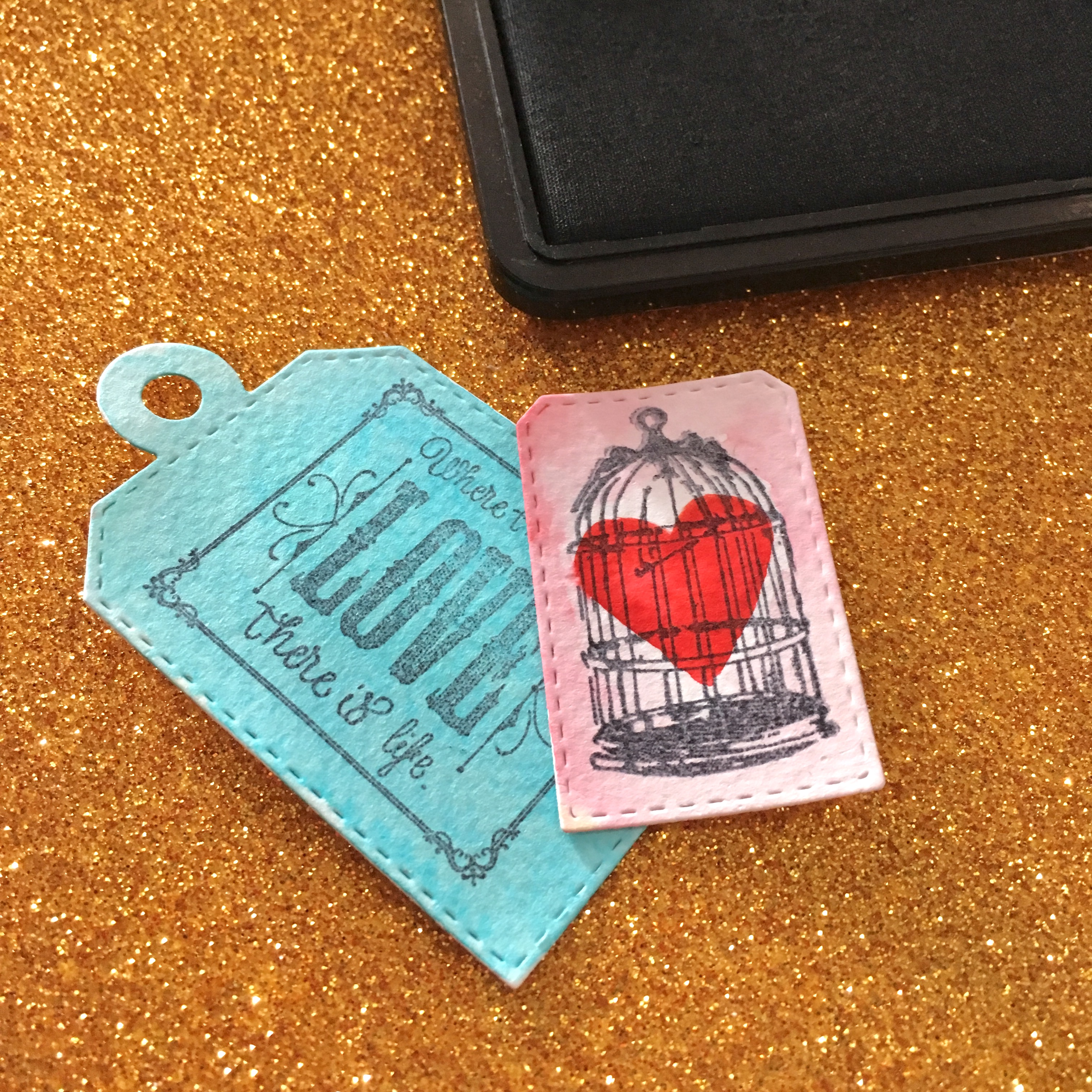 Blue and pink tags. The blue tag has stamp LOVE and the pink - a birdcage with a red heart inside