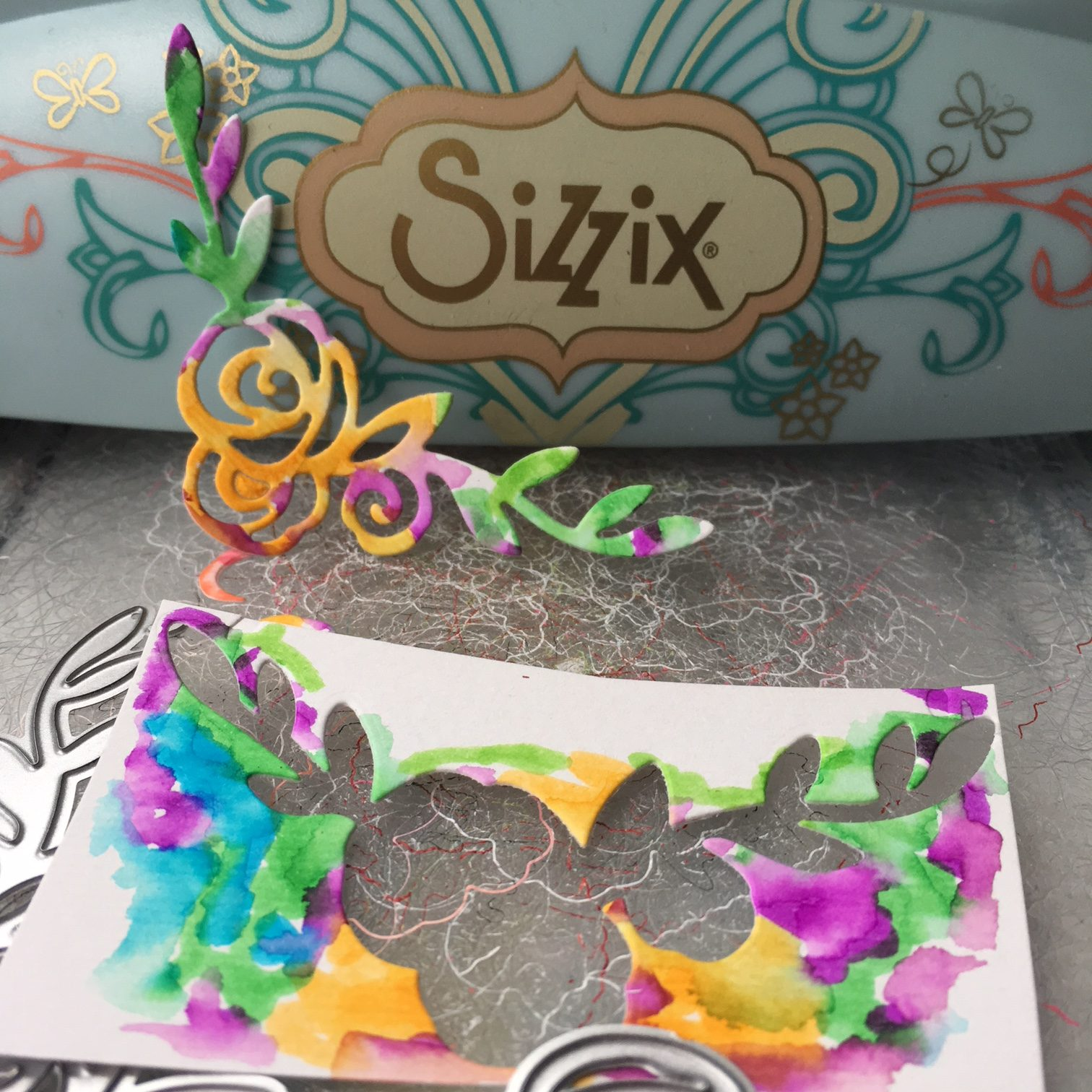 Sizzix Big shot machine and watercolour drawings on white paper and the result - colourful paper embellishments for greeting card decoration