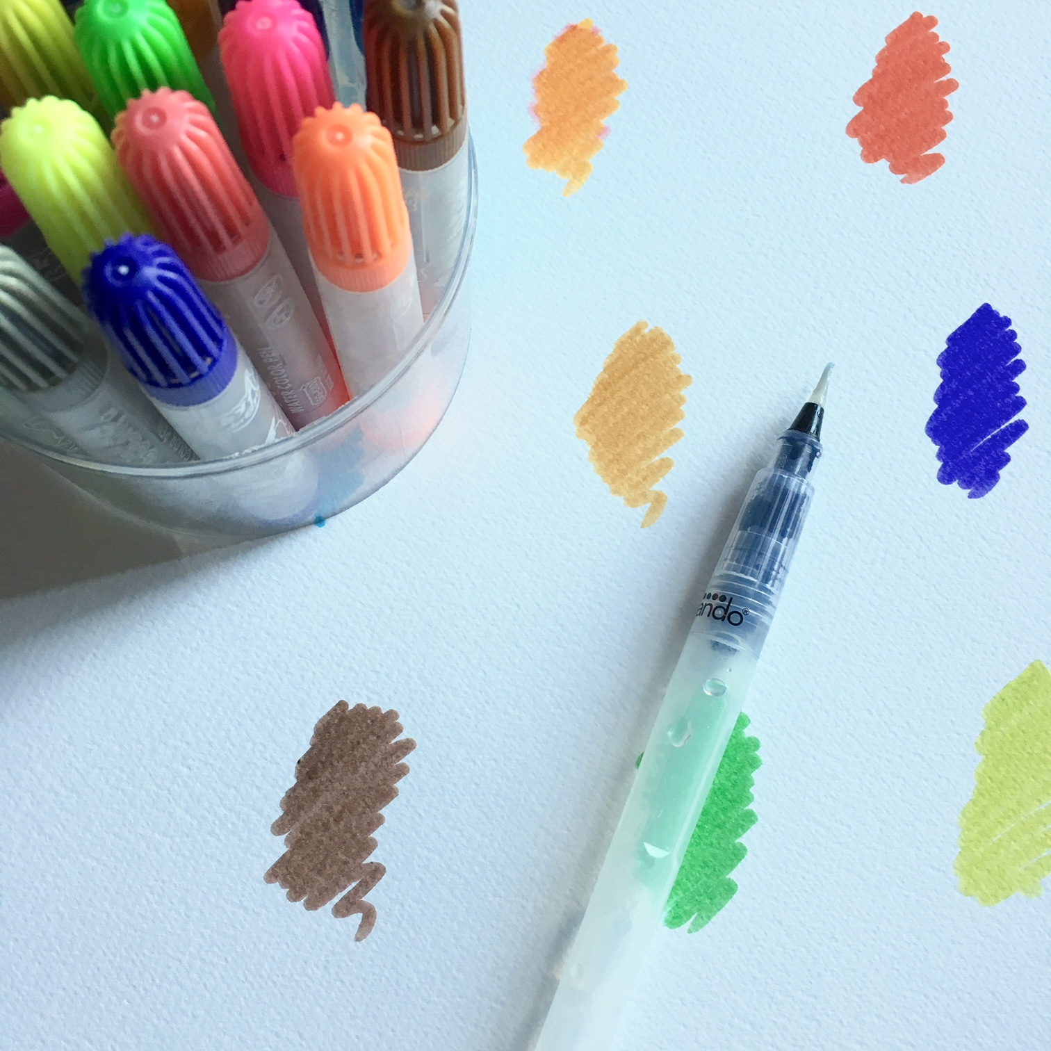 watercolour markers and a container brush, coloured small scribbles in brown, orange, blue, green, yellow...