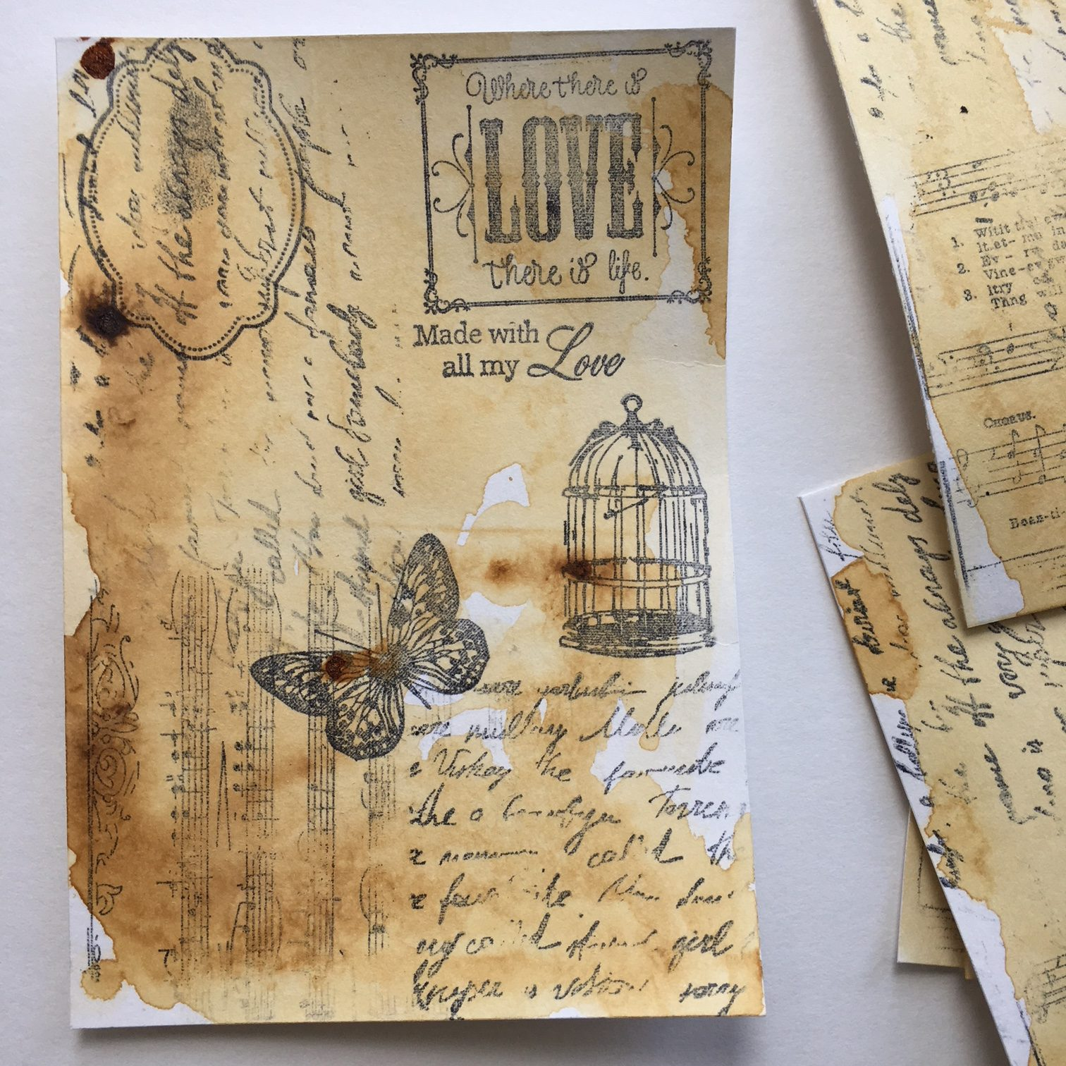 """the brown coffee coloured background with """"love"""", letter, cage and butterfly stamps in black"""