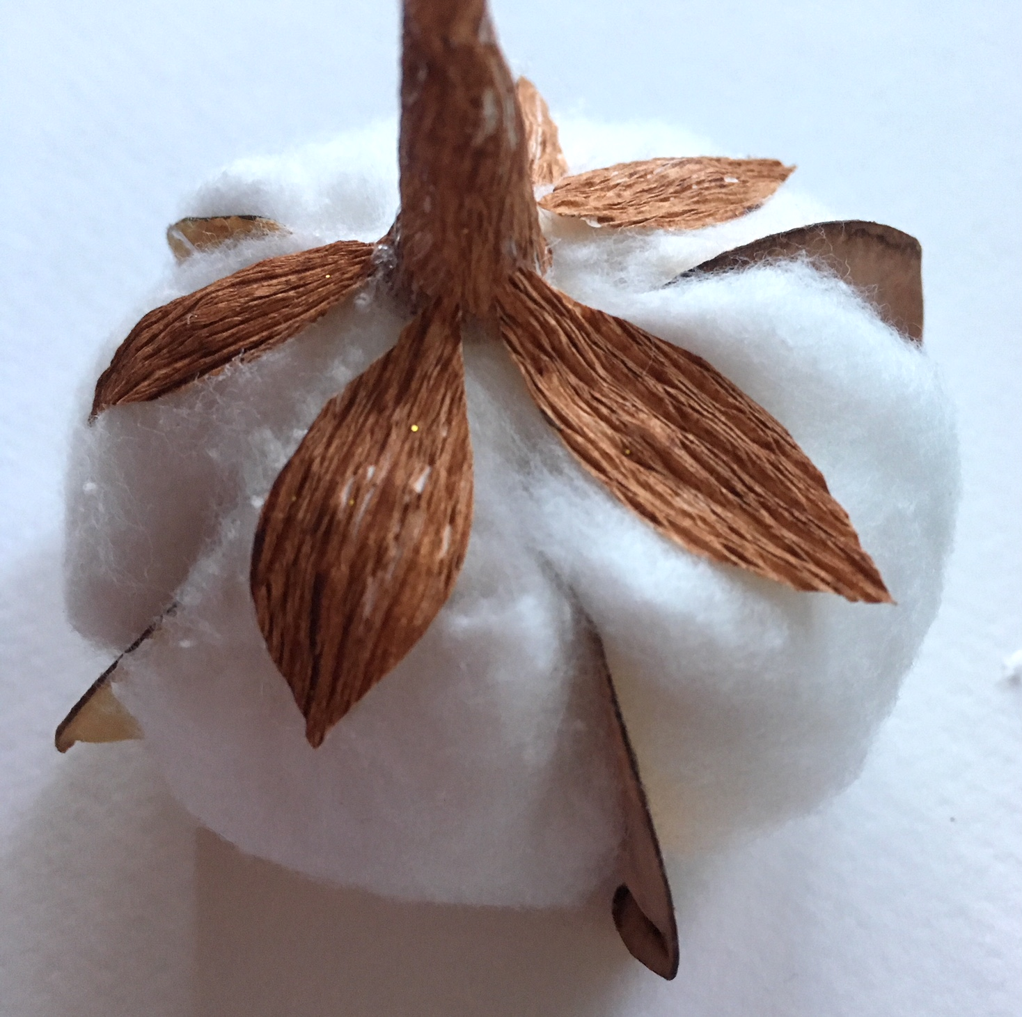 little brown leaves glued on the white cotton