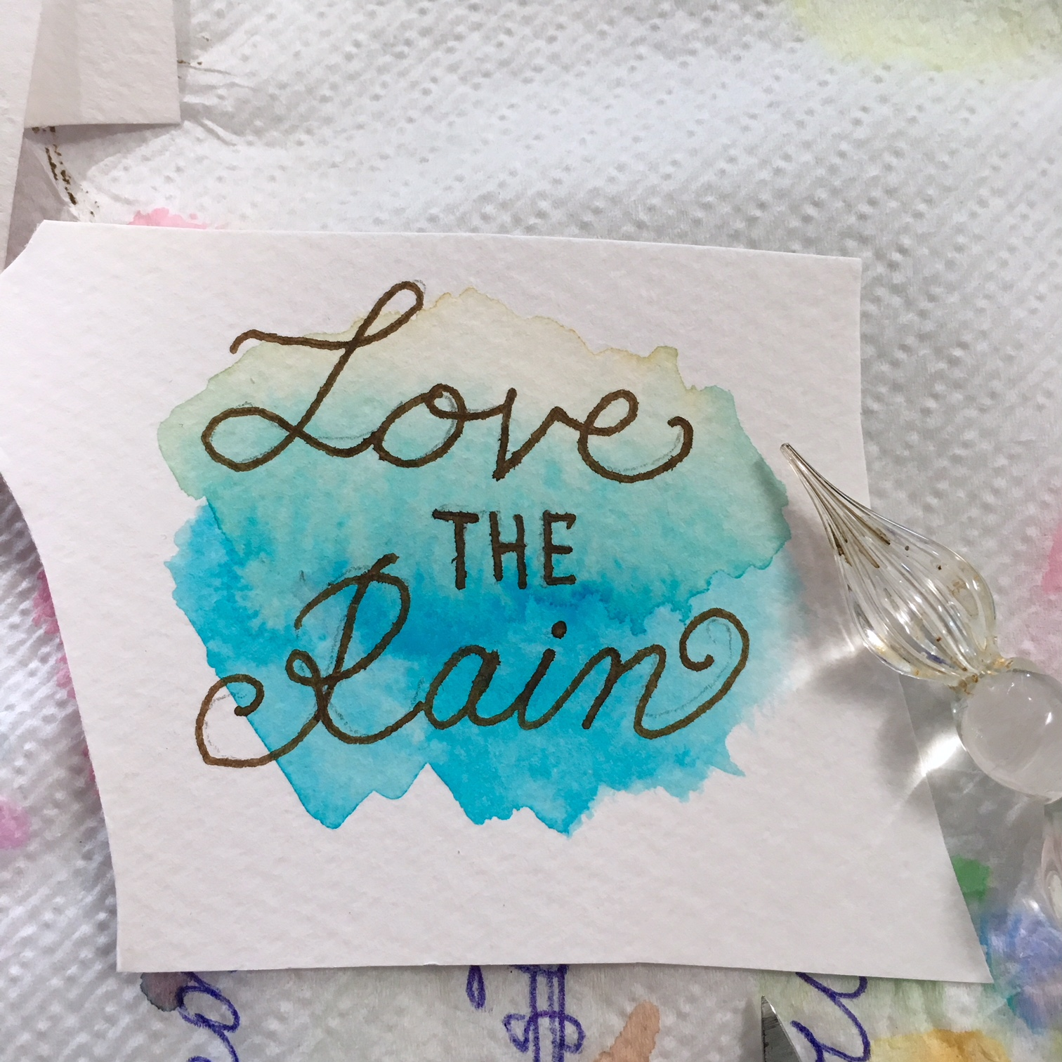 """white watercolour paper with blue-brown watercolour spot and written """"Love the rain"""", also a glass ink pen"""