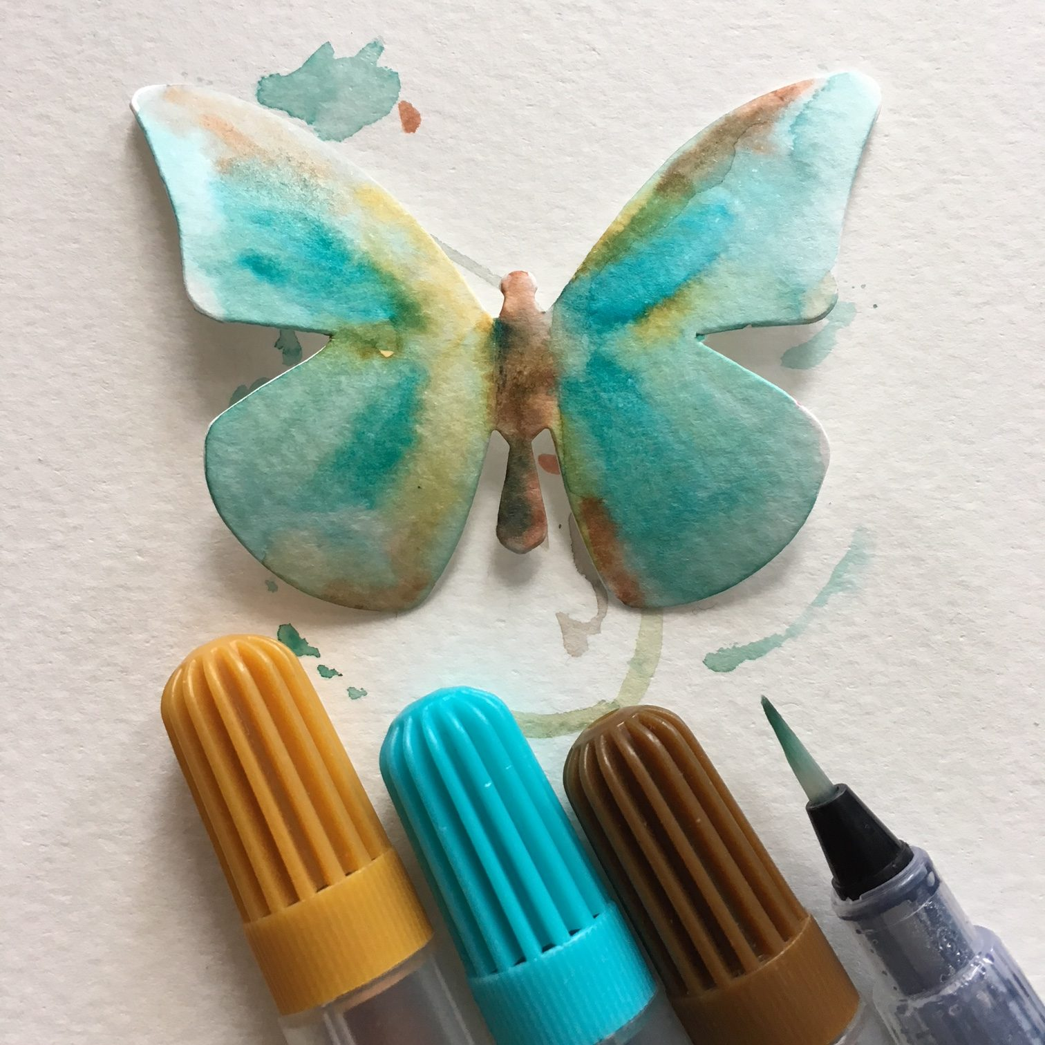 paper butterfly coloured in blue and brown and blue and brow watercolour markers and water container brush