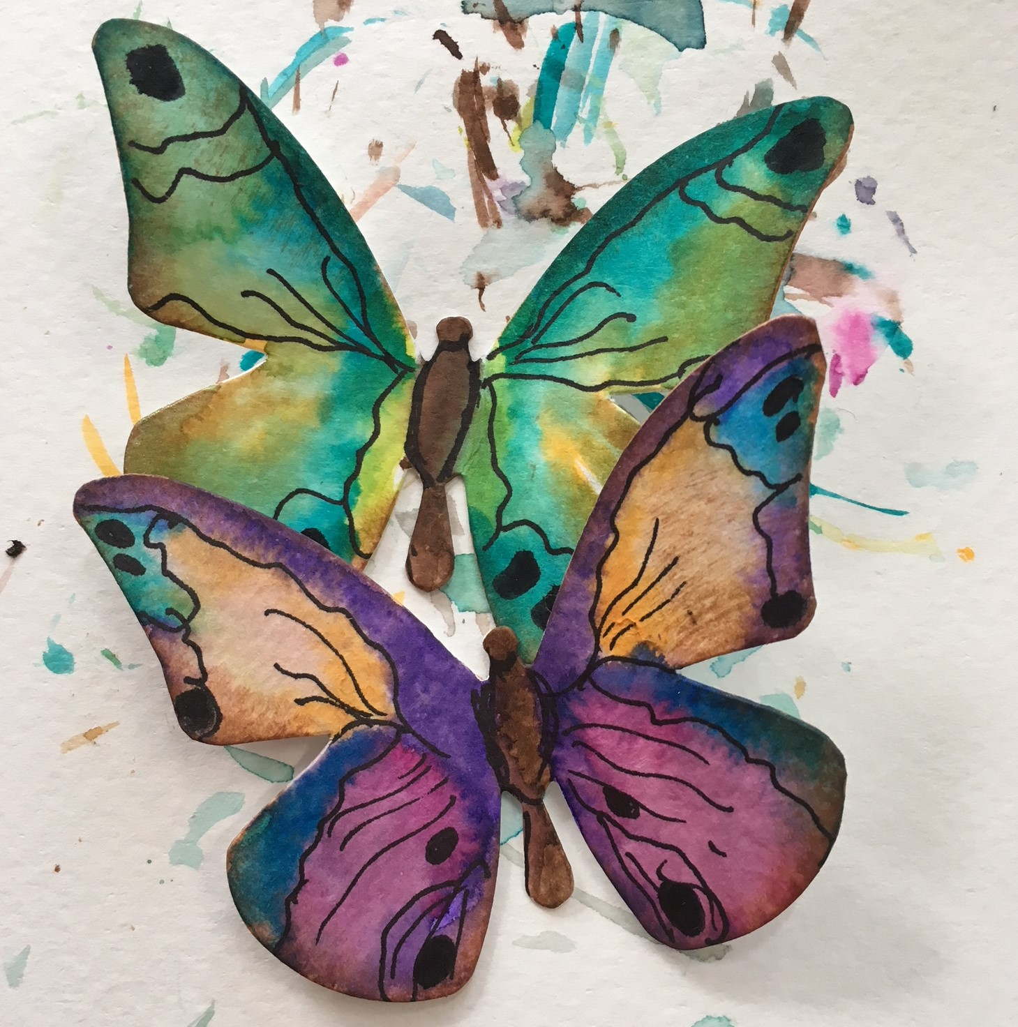 paper butterflies watercoloured in purple, blue turquoise, orange and black