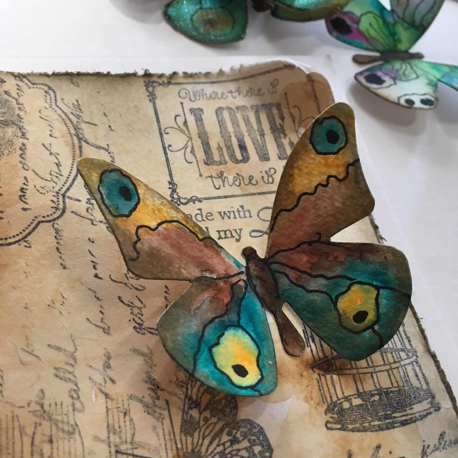 paper butterfly in orange, blue and brown, glued on brown vintage paper piece with stamps