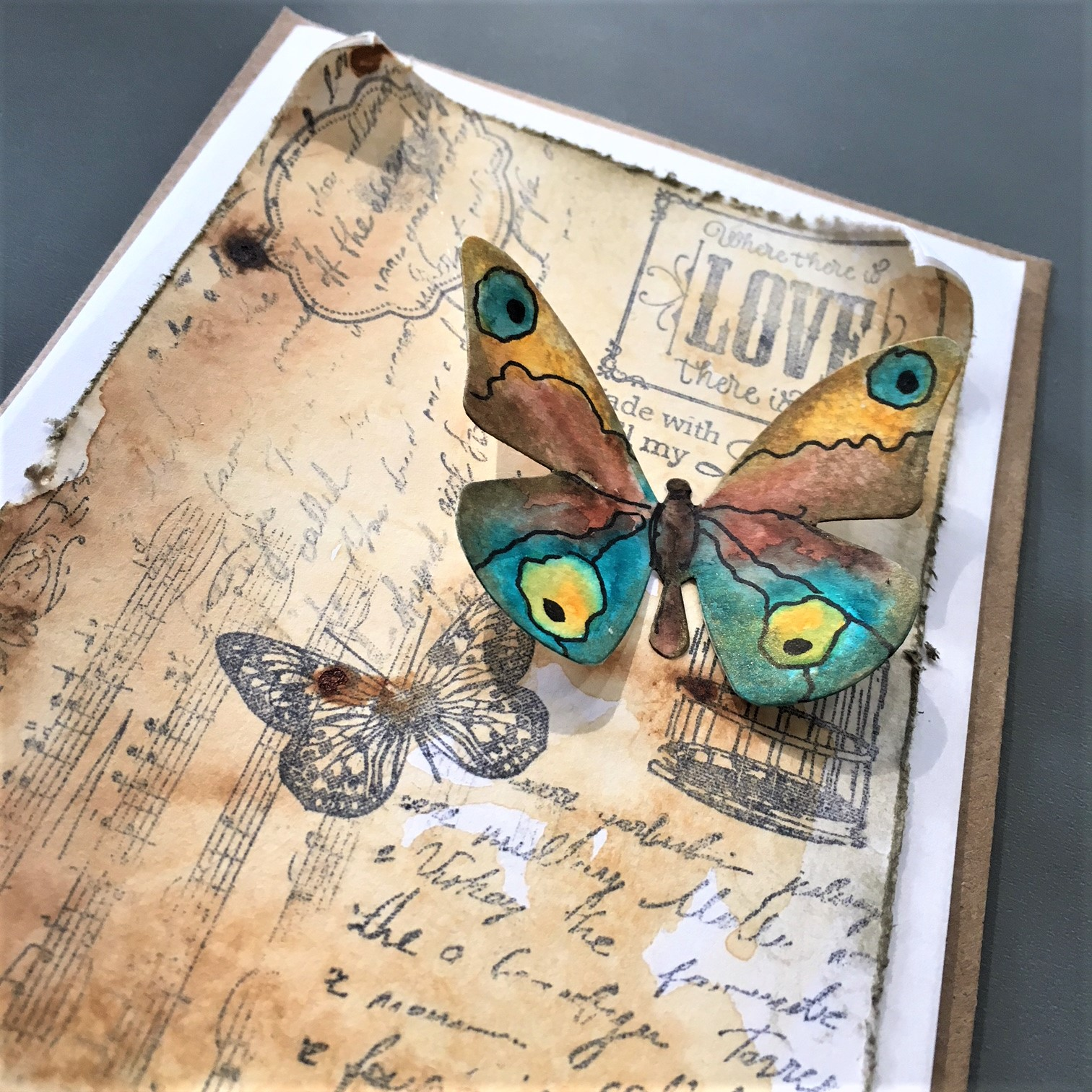greeting card with a vintage brown-sepia background and a paper butterfly in orange, blue and brown
