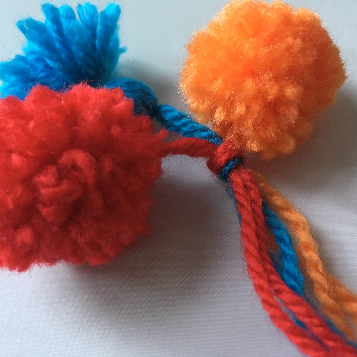 wool pompoms in blue, red and orange
