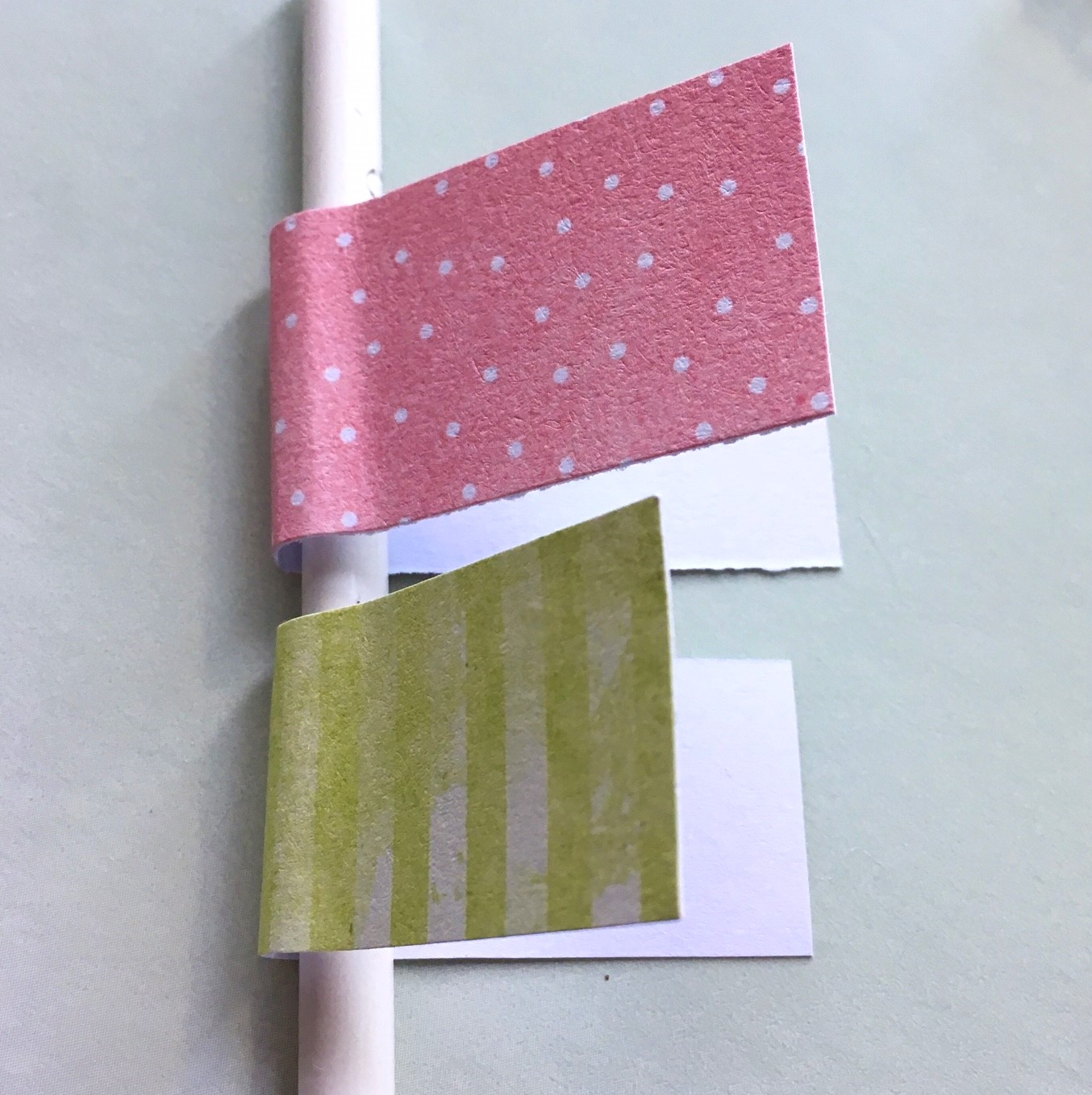 coloured paper rectangles twisted around pencils