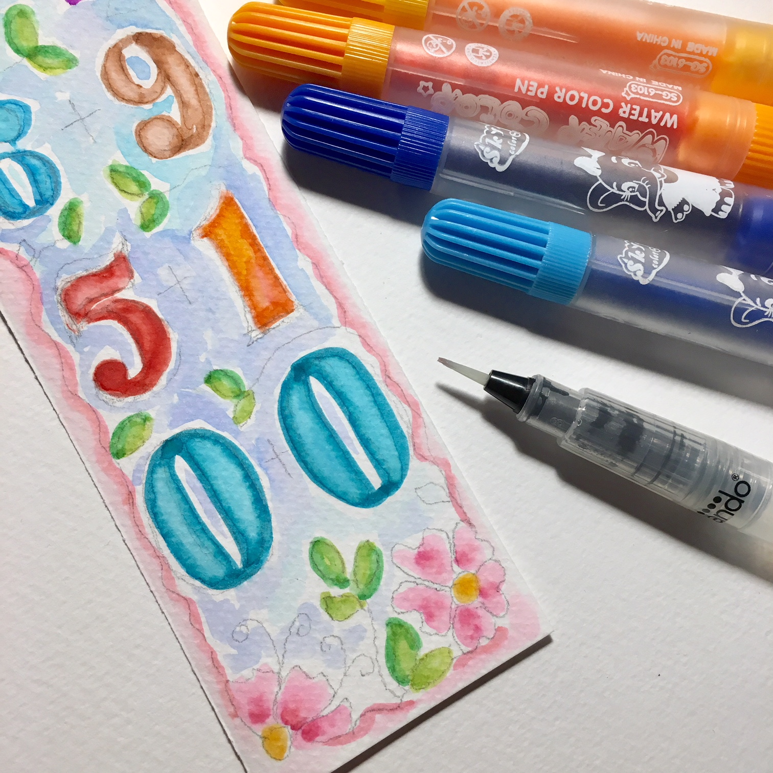 colouring the numbers with watercolour markers and a container brush