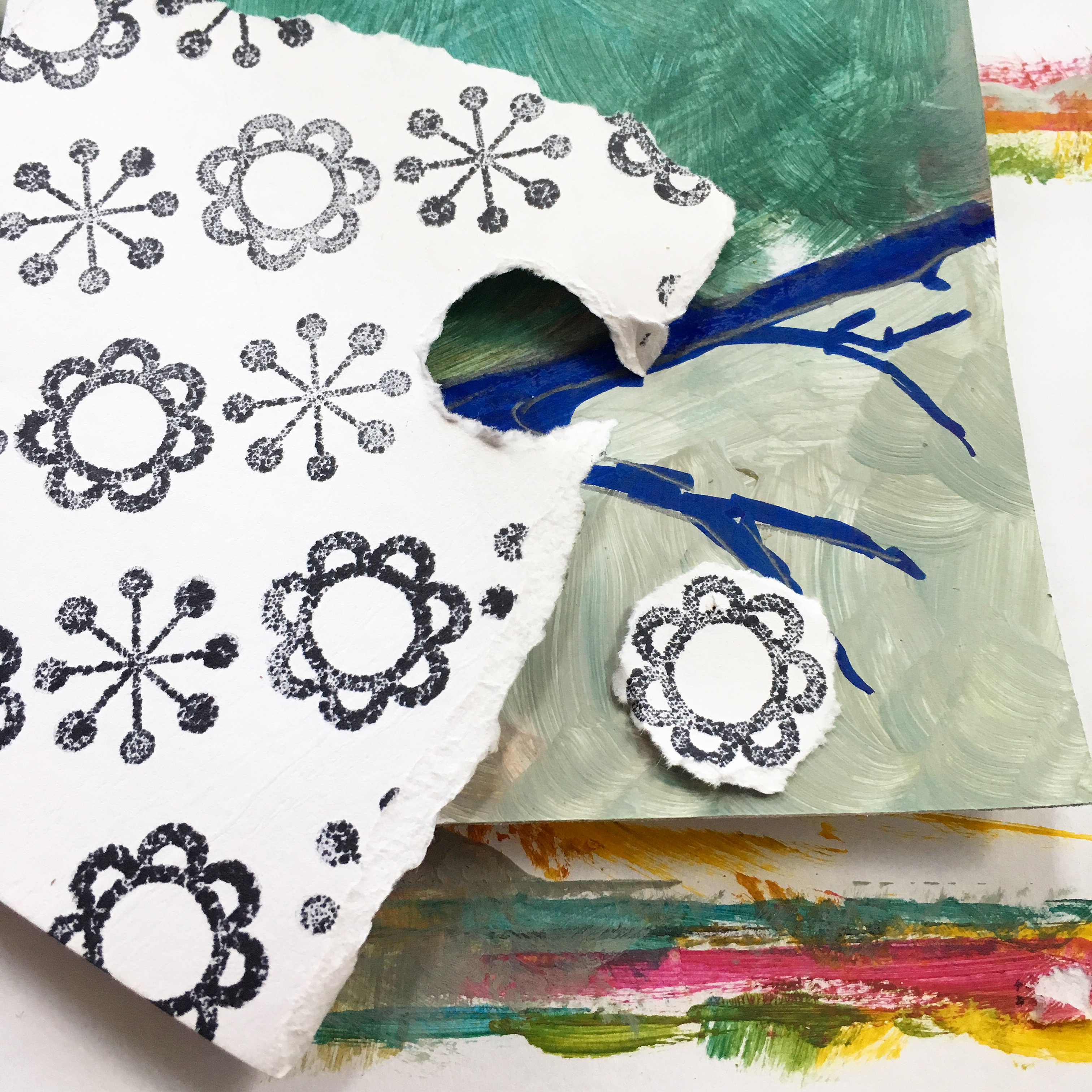 white piece of paper with black snowflake and flower stamps, one of the flowers is torn around the edges