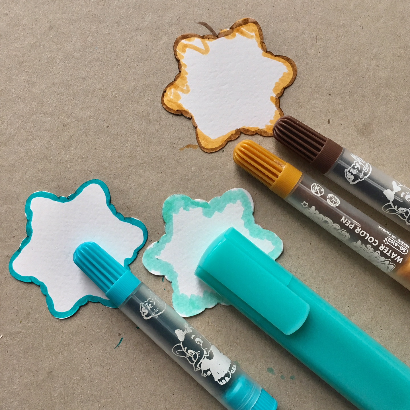 drawing with brown and blue markers on paper cookie shapes