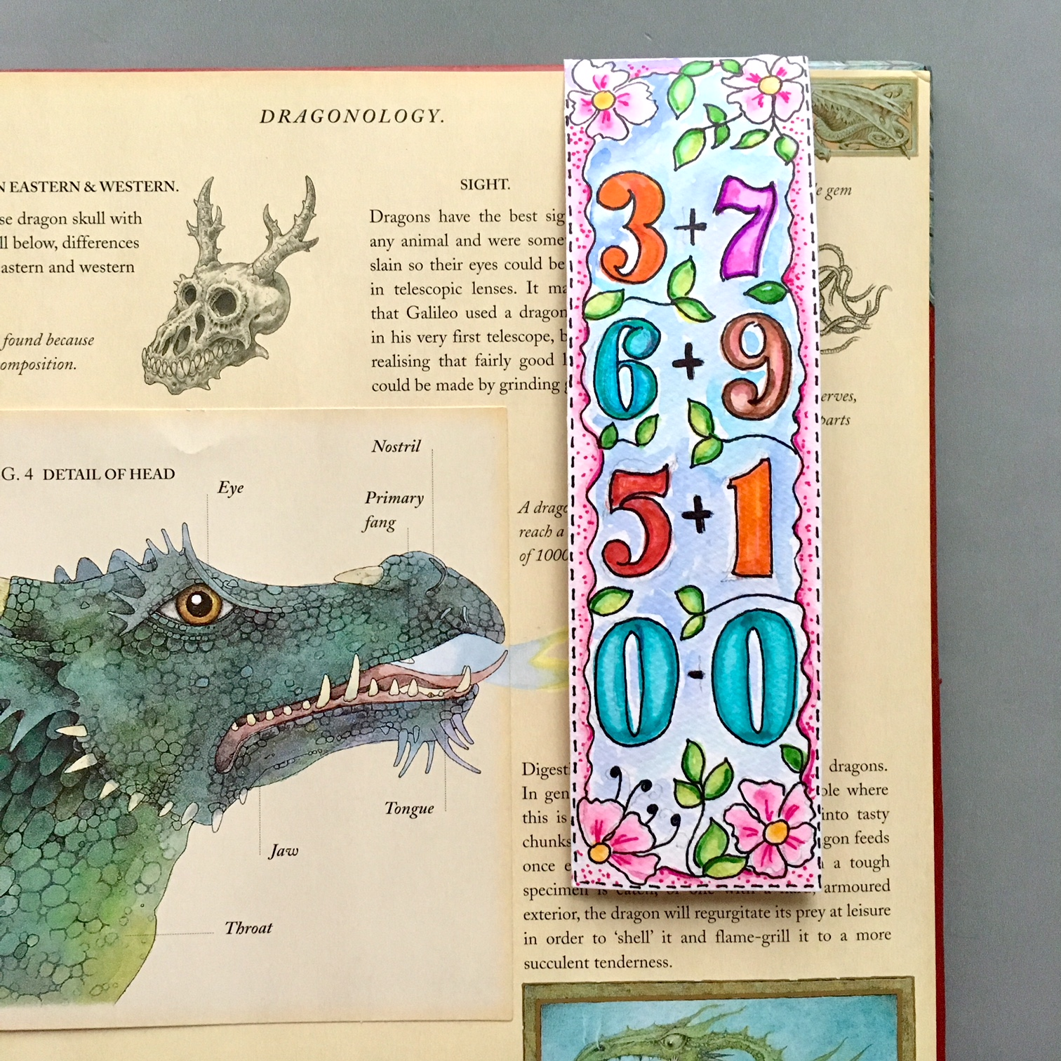 book page with dragons and a handmade bookmark with numbers in different colours