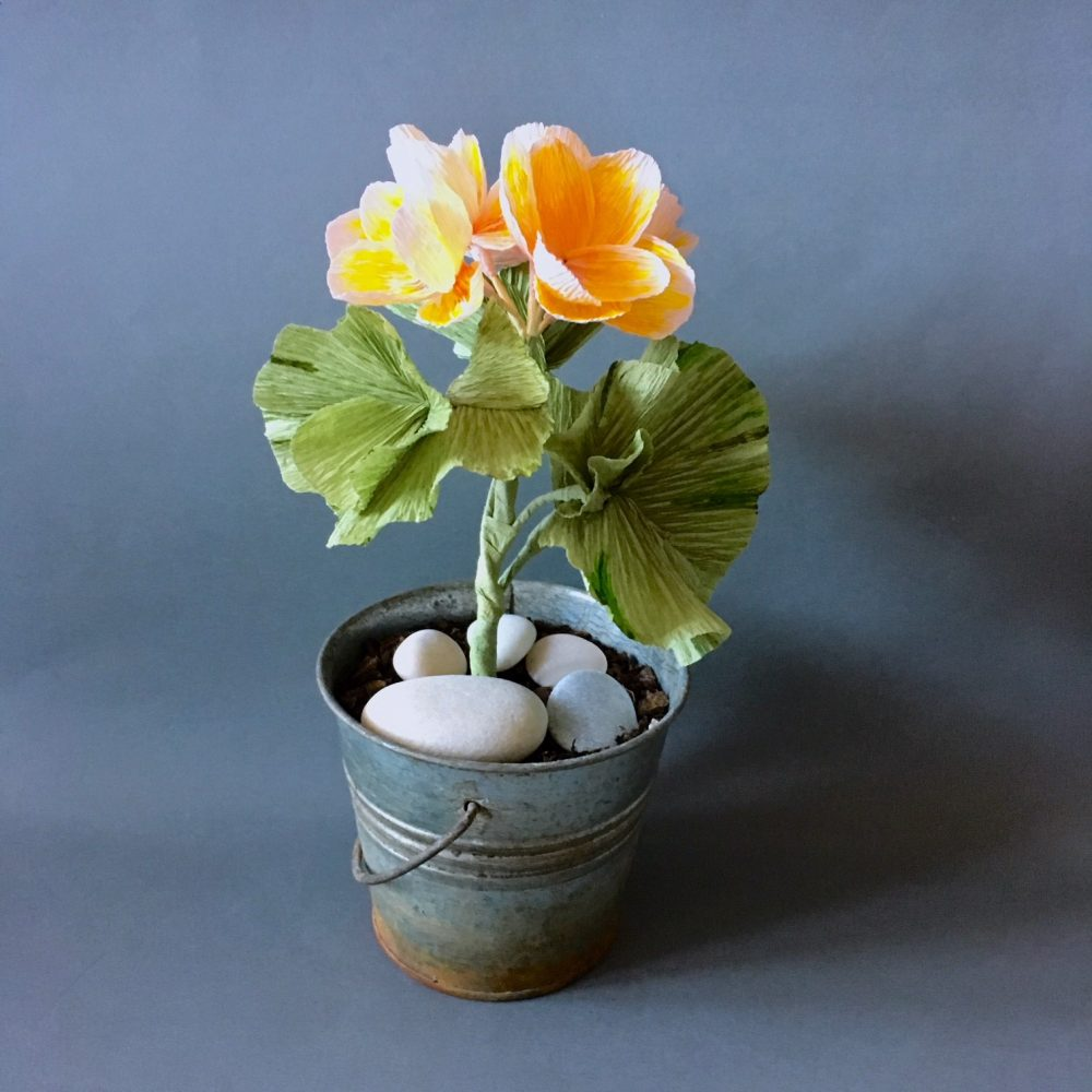 finished crepe paper yellow pelargonium in metal flower pot with white stones