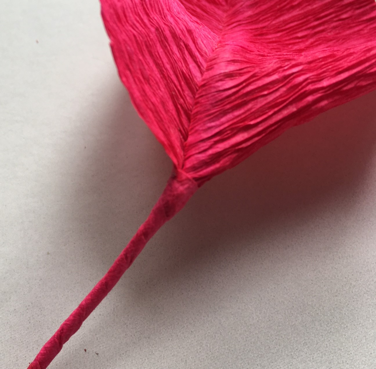 the stem ot the red crepe paper leaf, covered with red crepe paper too