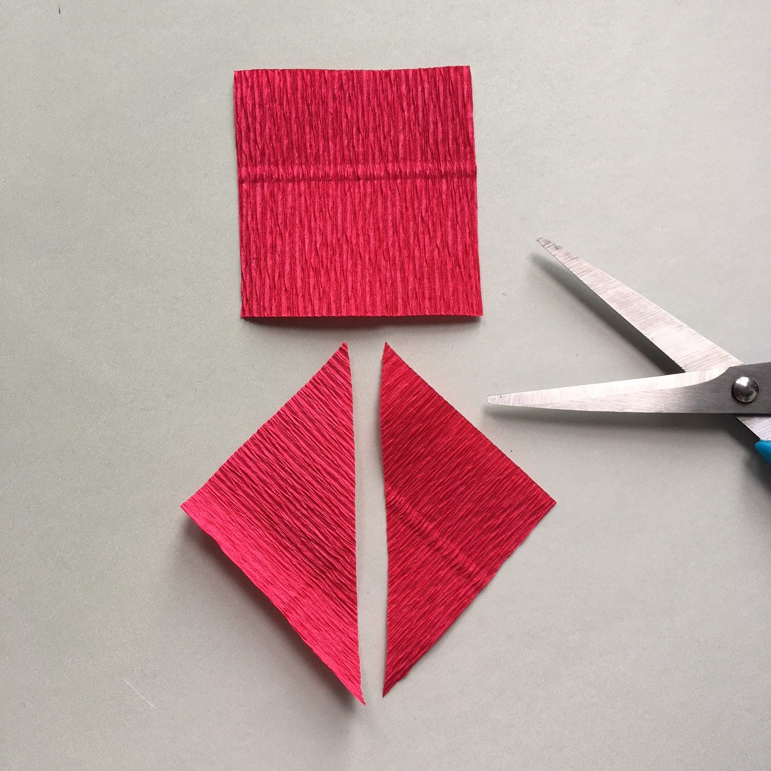 square piece of red crepe paper diagonally cut