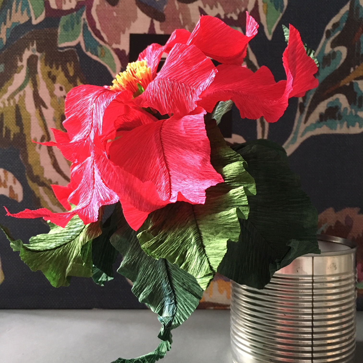 crepe paper Poinsettia in a tin can with floral background
