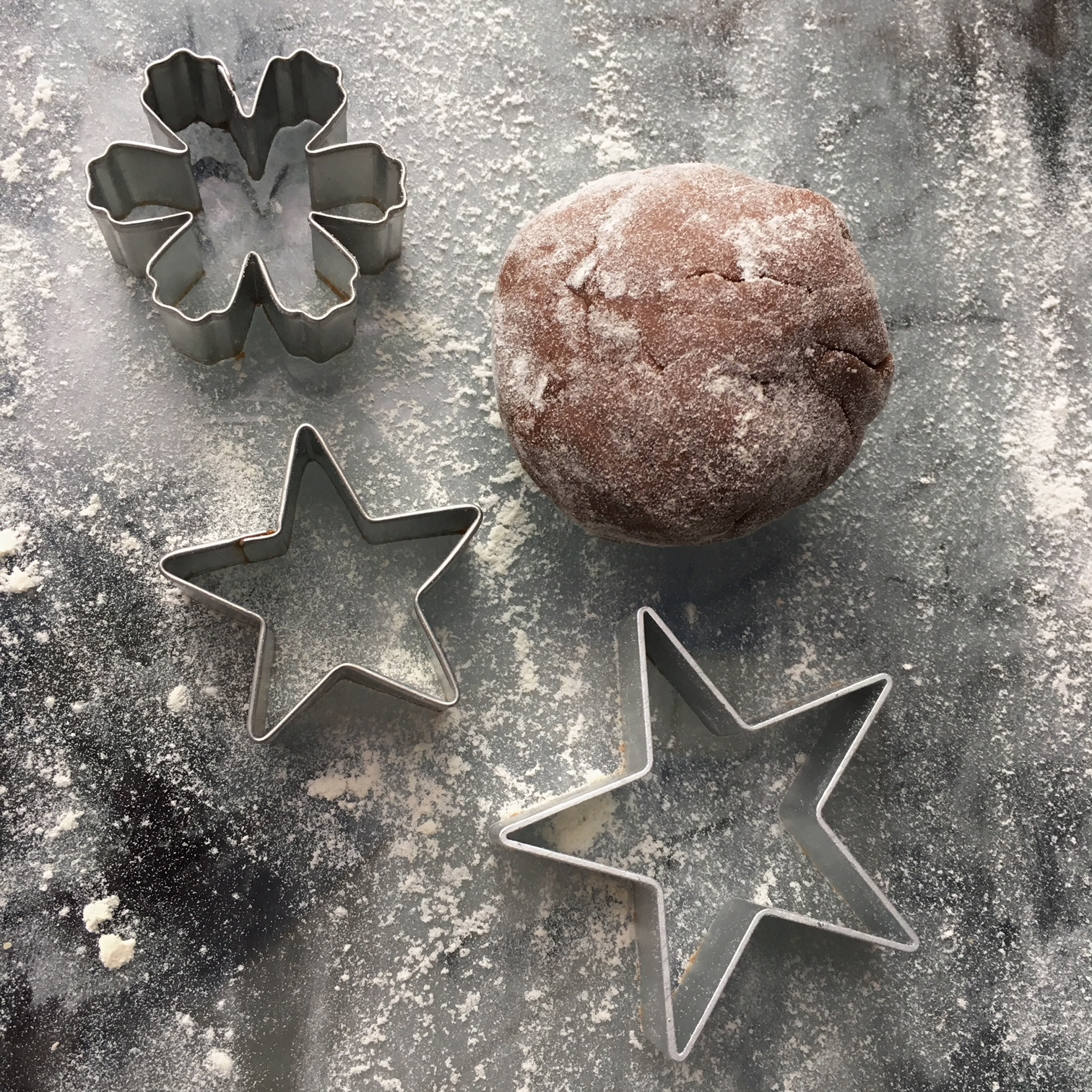 a ball of gingerbread dough and star and snowflake cutters