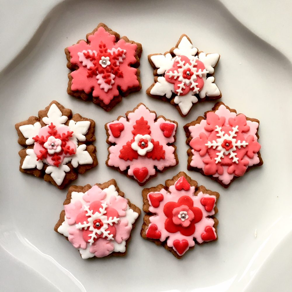 Christmas gingerbread cookies in a snowflake shape, decorated in white, pink, red and gold