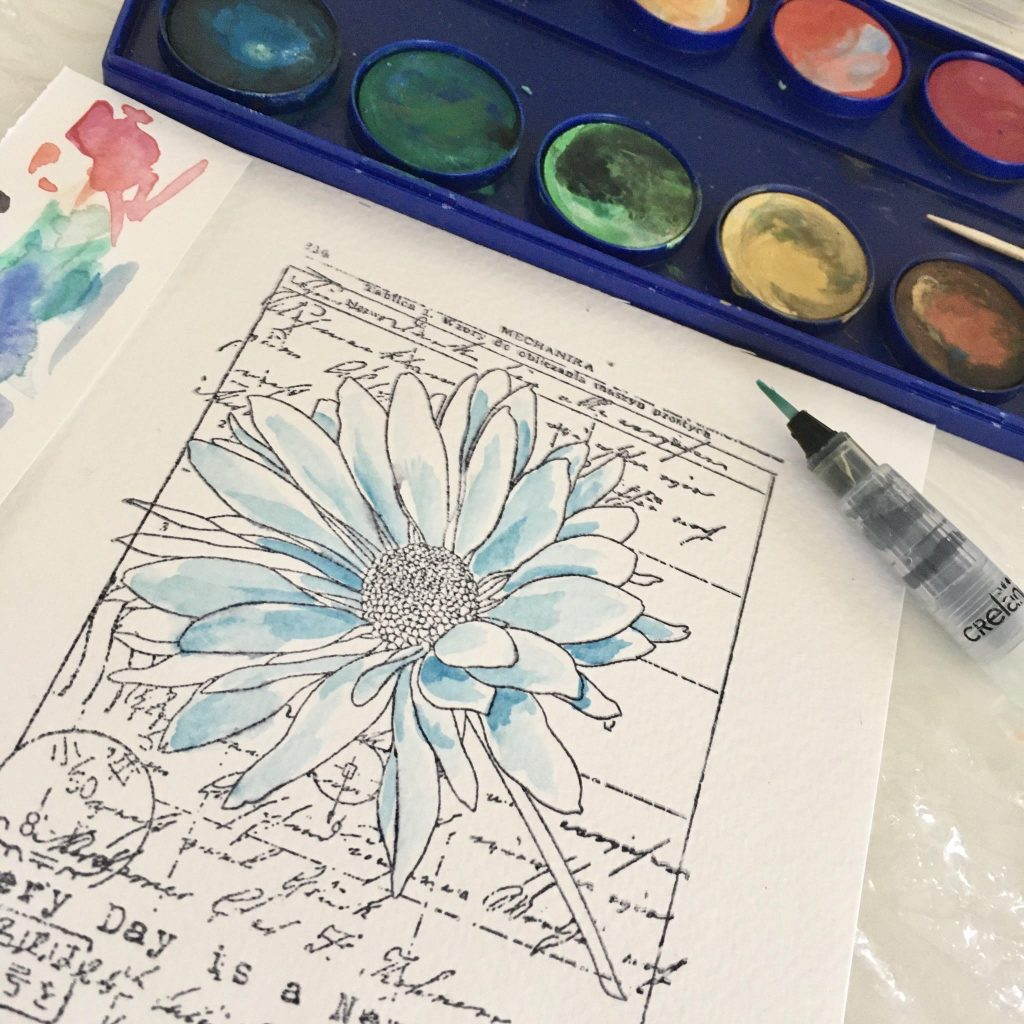using watercolours and water container brush to colour the stamp. Water container brushes are great for kids
