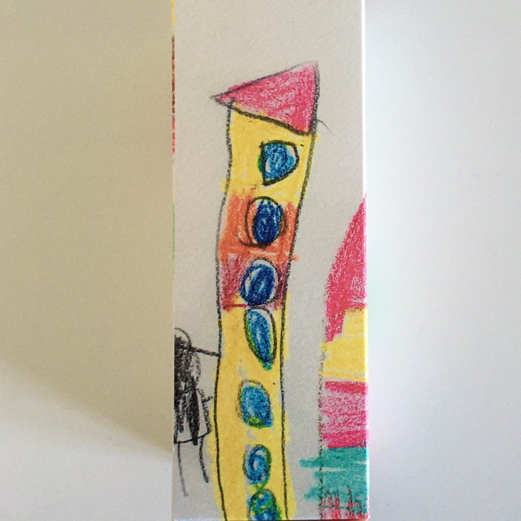 Kid's hand drawing of a tower looking house in yellow and red with blue round windows