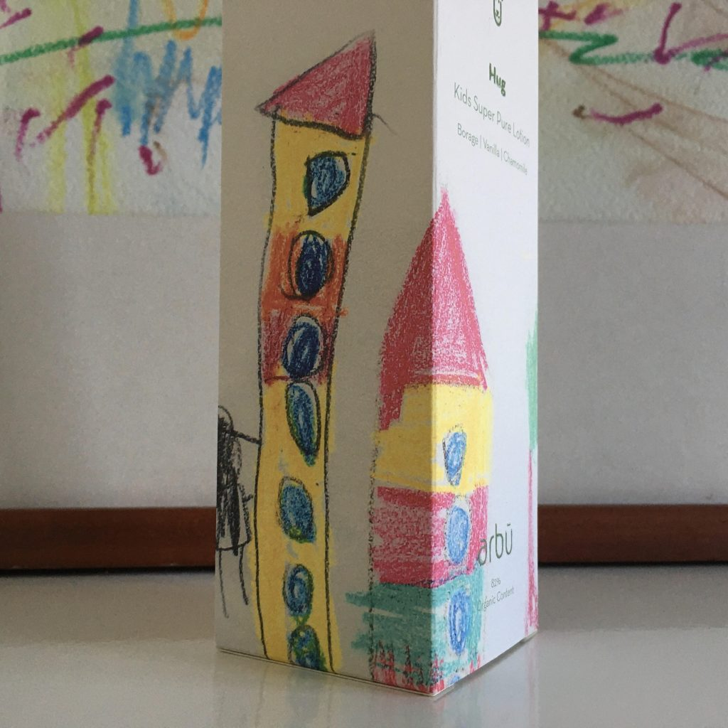 white paper box with kid's drawing of houses in red and yellow with blue windows